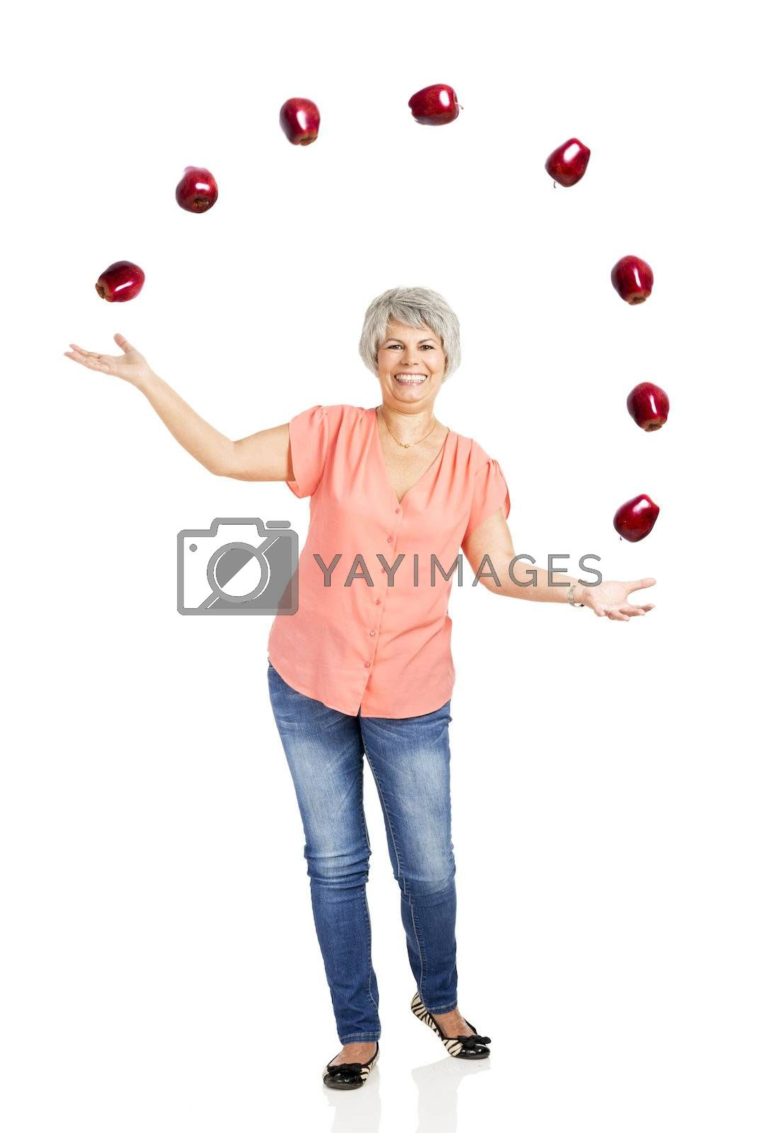 Royalty free image of Old woman throwing apples by Iko
