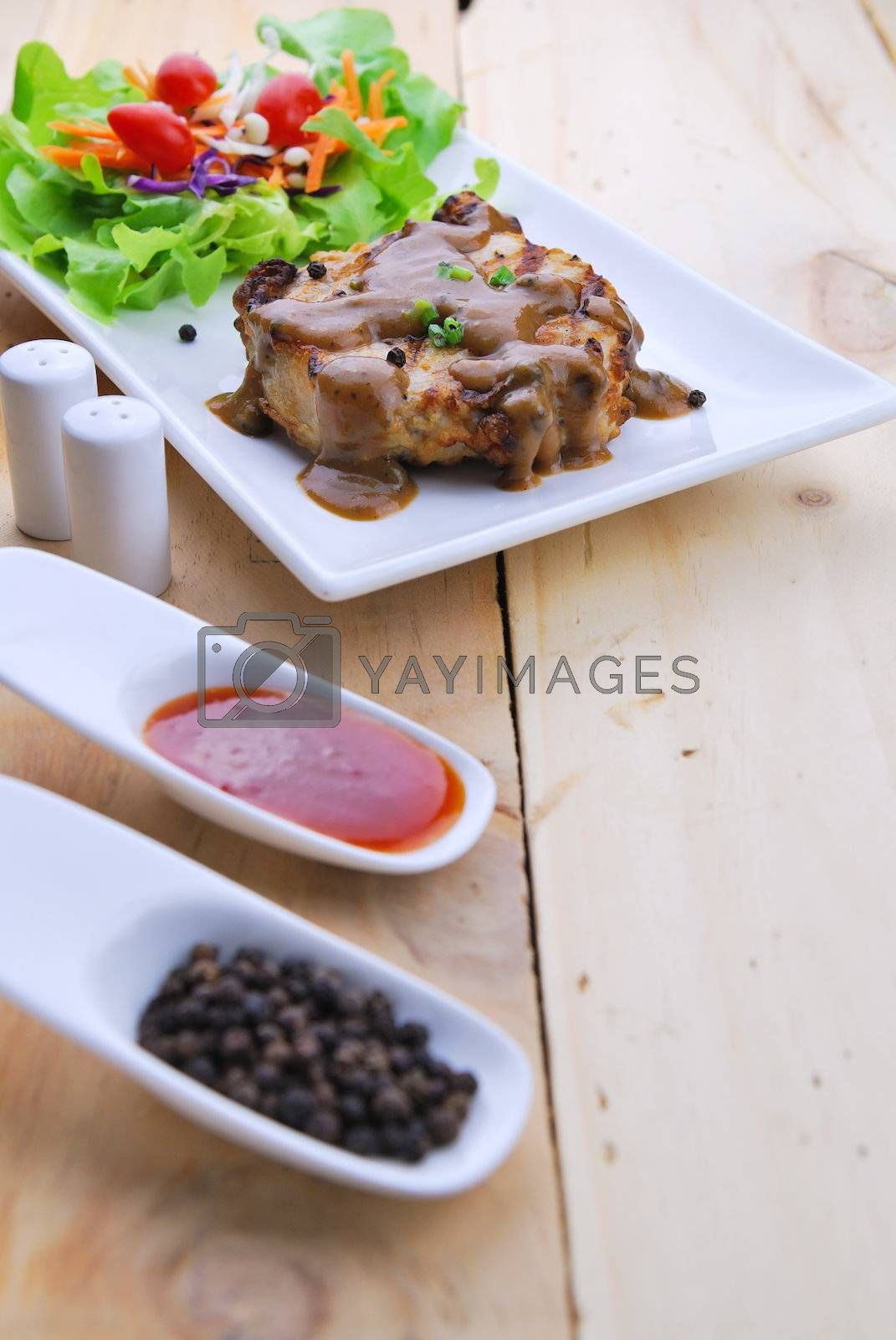 Royalty free image of Grilled steaks, pork with pepper gravy and vegetable salad  by teen00000