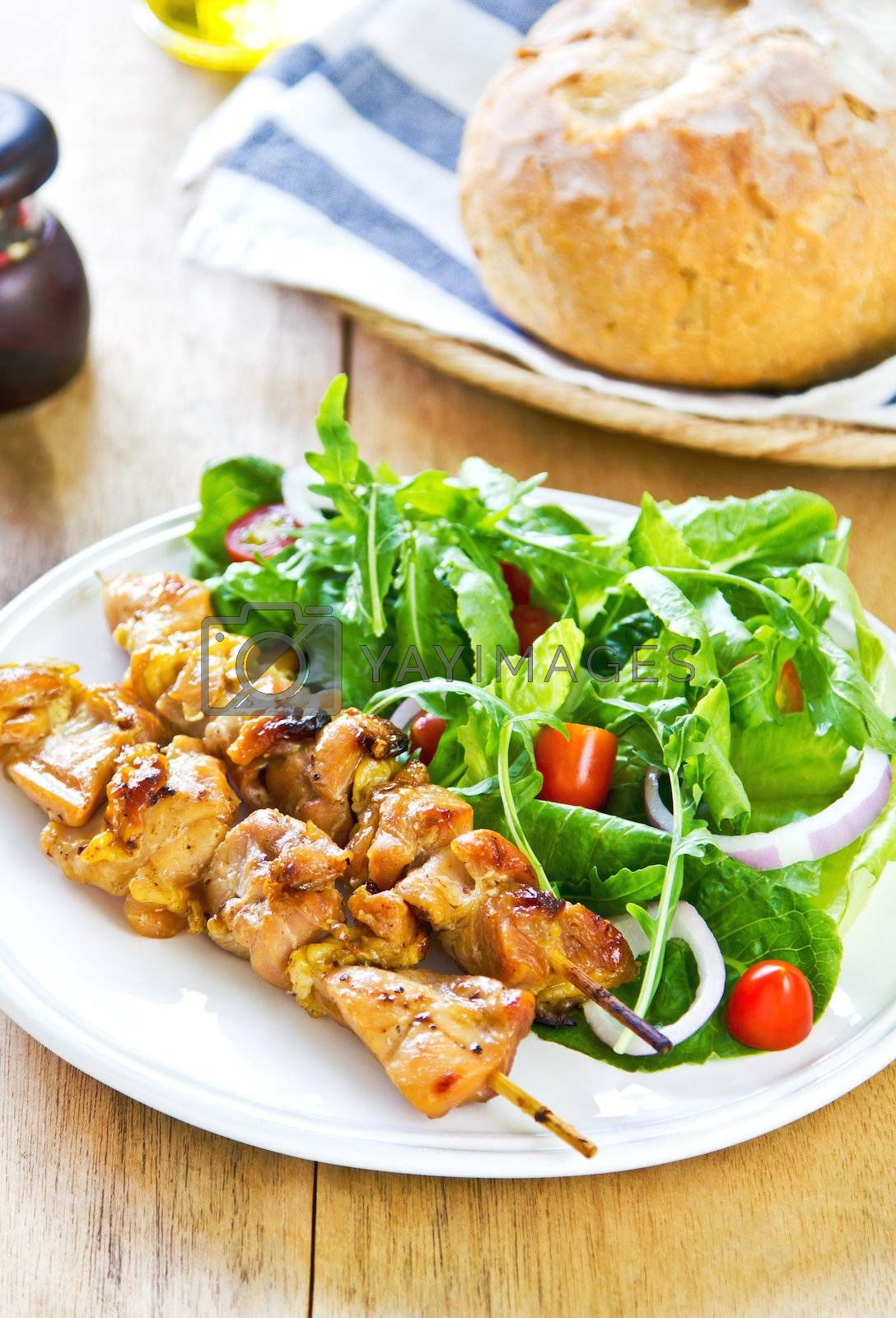 Royalty free image of Grilled chicken skewer with salad by vanillaechoes
