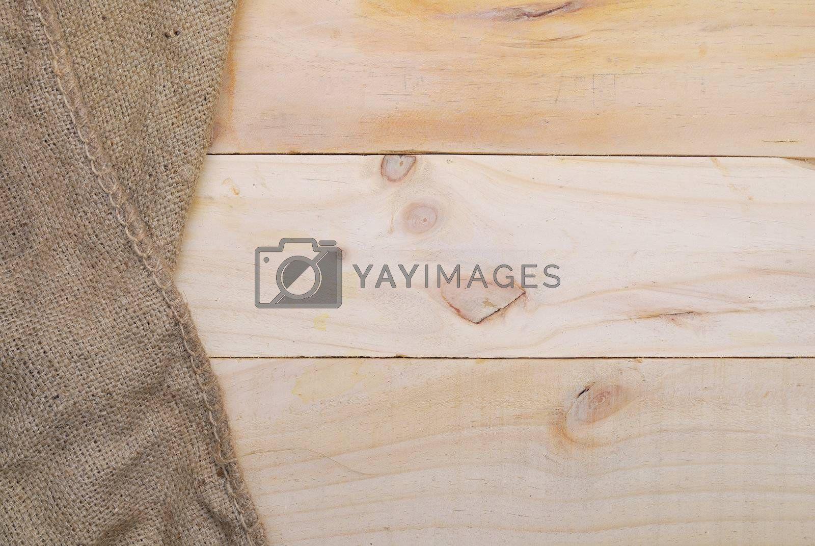 Royalty free image of Gunny sack texture and wood plank table background by teen00000