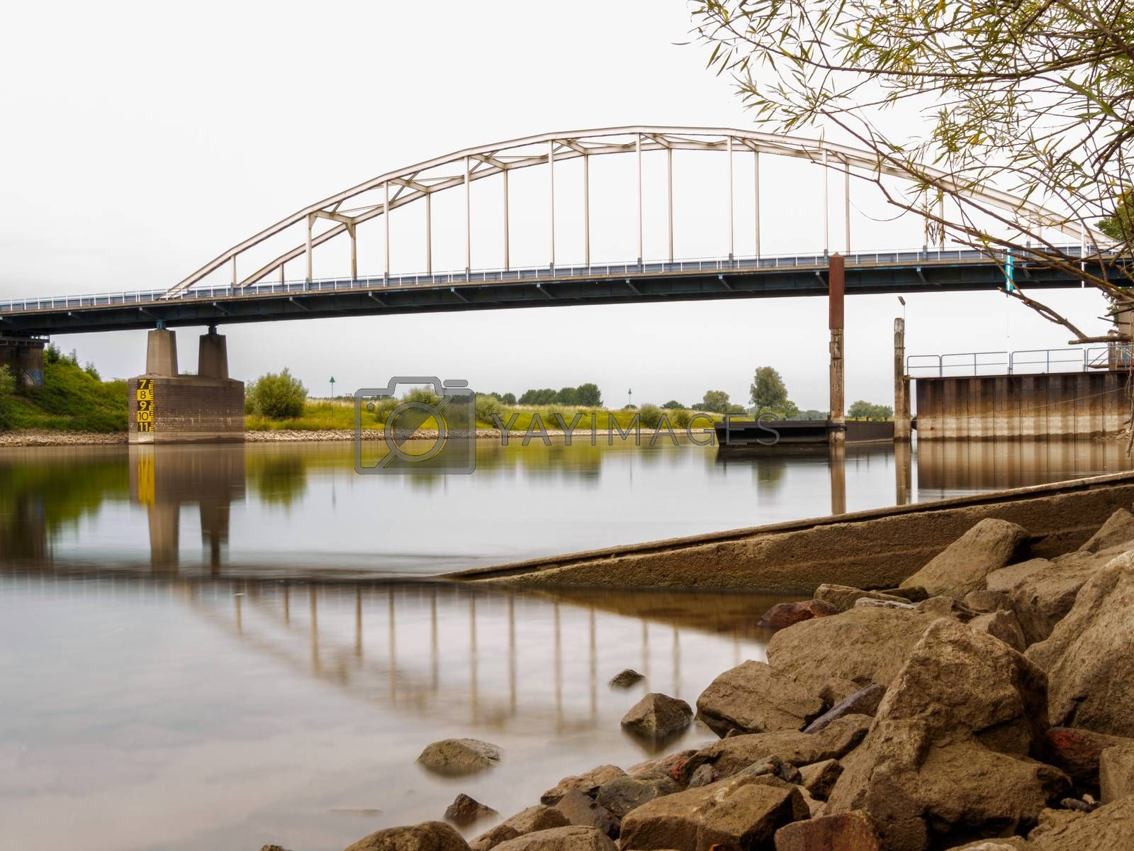 Royalty free image of Smooth water looking past rocks at a bridge across a river by frankhoekzema