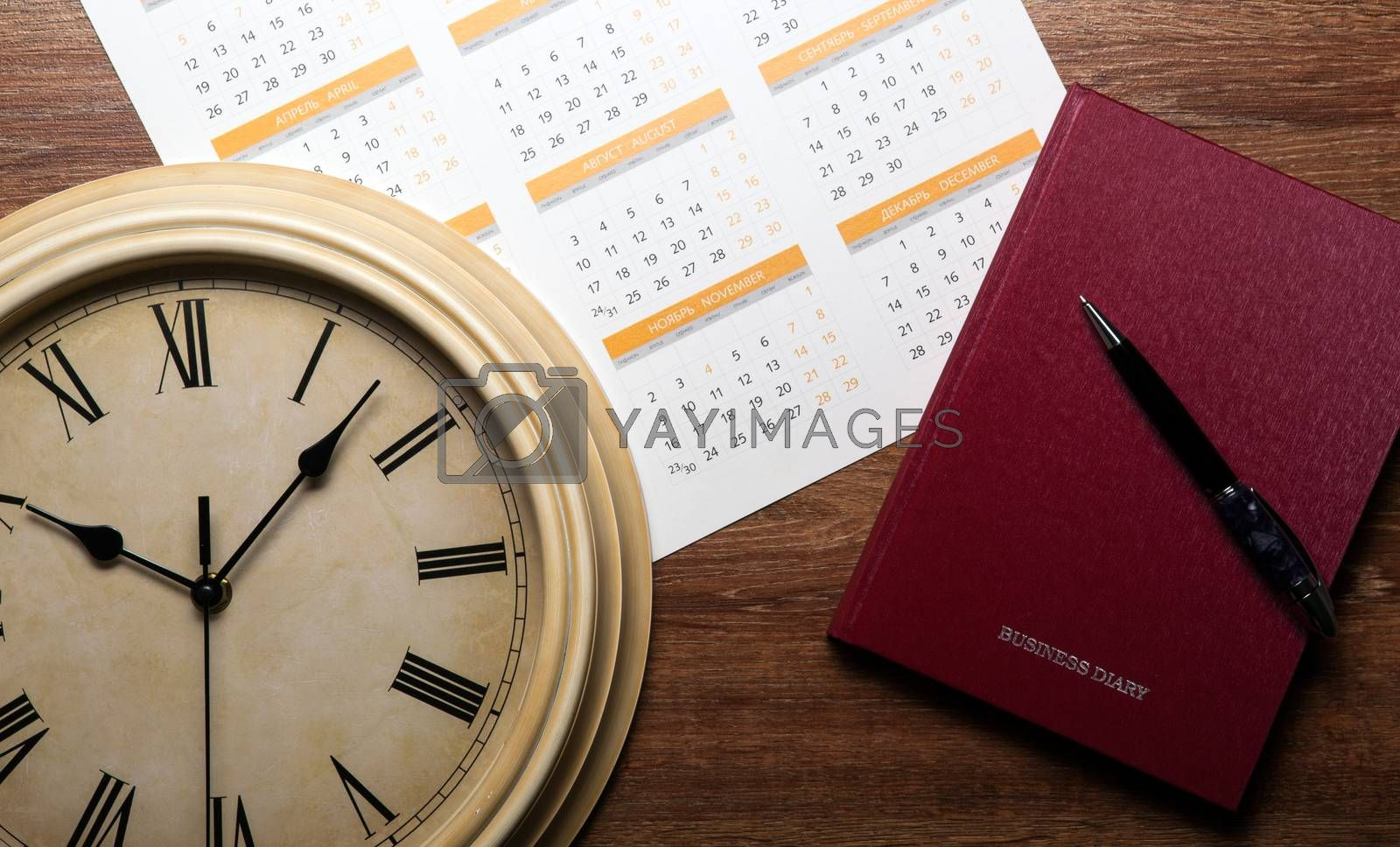 Royalty free image of diary with large pen on the oak desk by mizar_21984