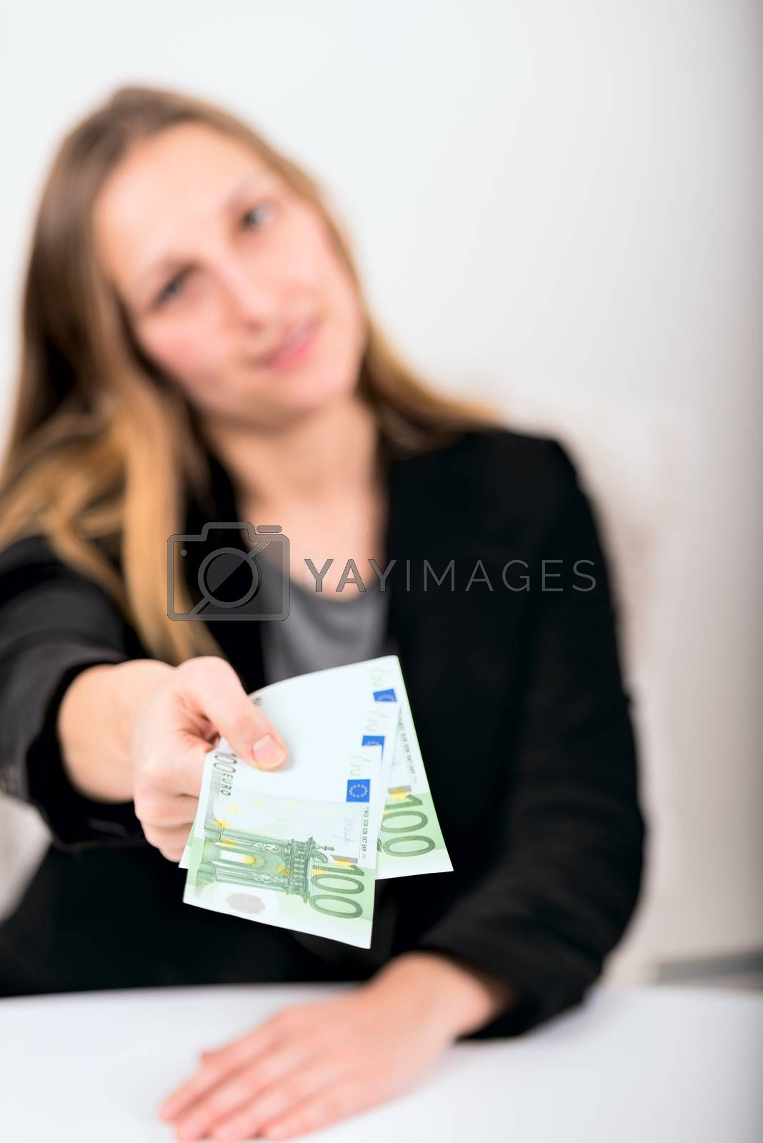 Royalty free image of young woman giving money by Nanisimova