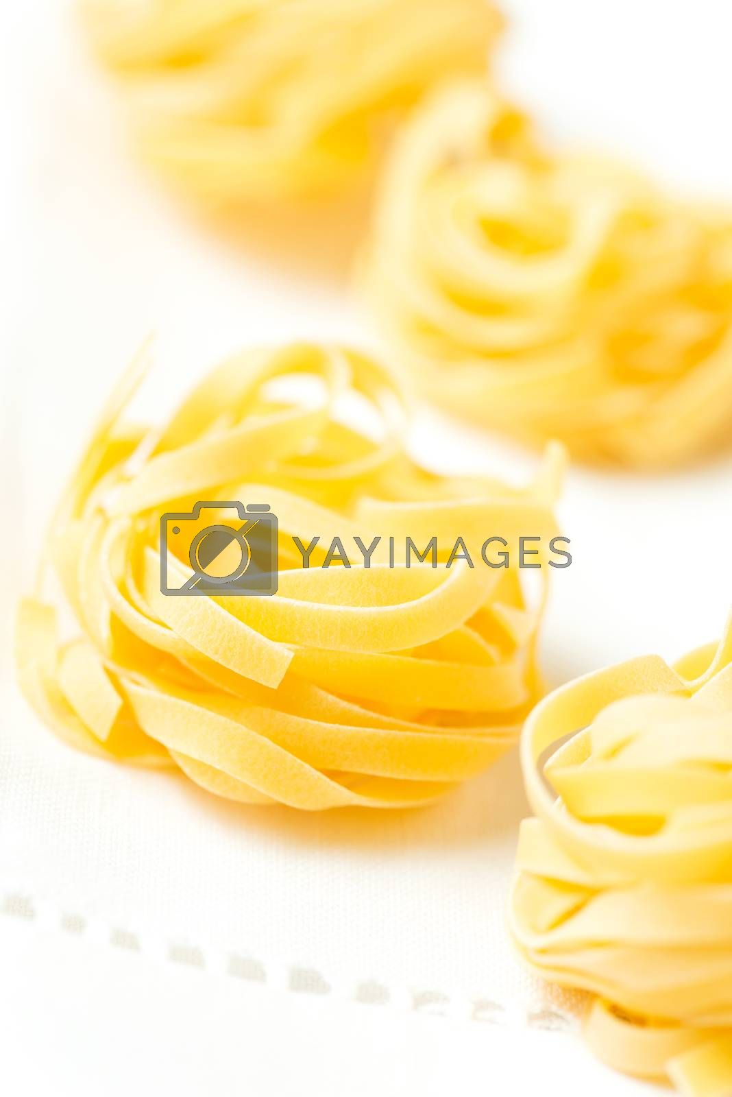 Royalty free image of Nests of pasta tagliatelle on tablecloth vertical by Nanisimova