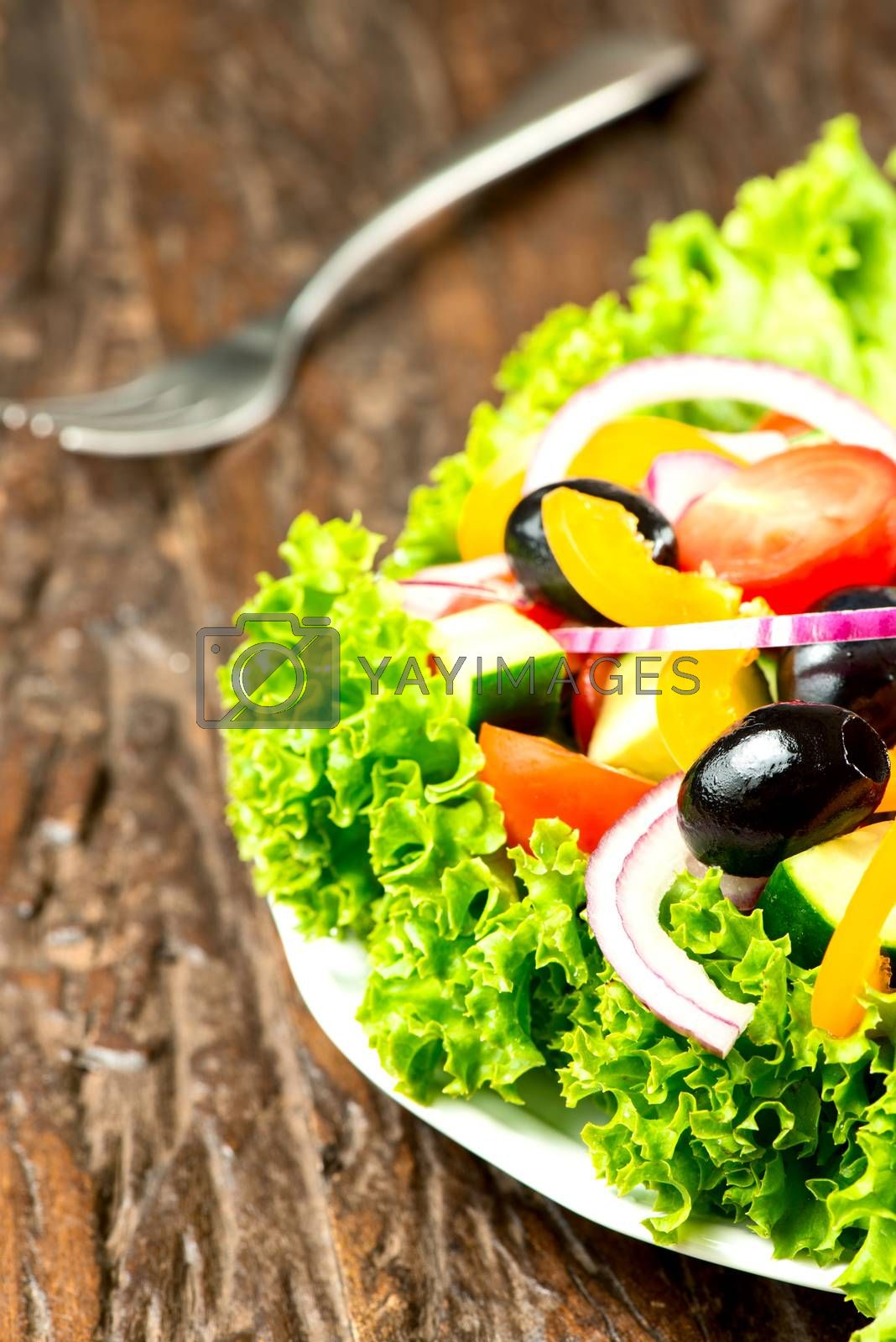 Royalty free image of Salad with vegetables and greens in plate on wooden table by Nanisimova