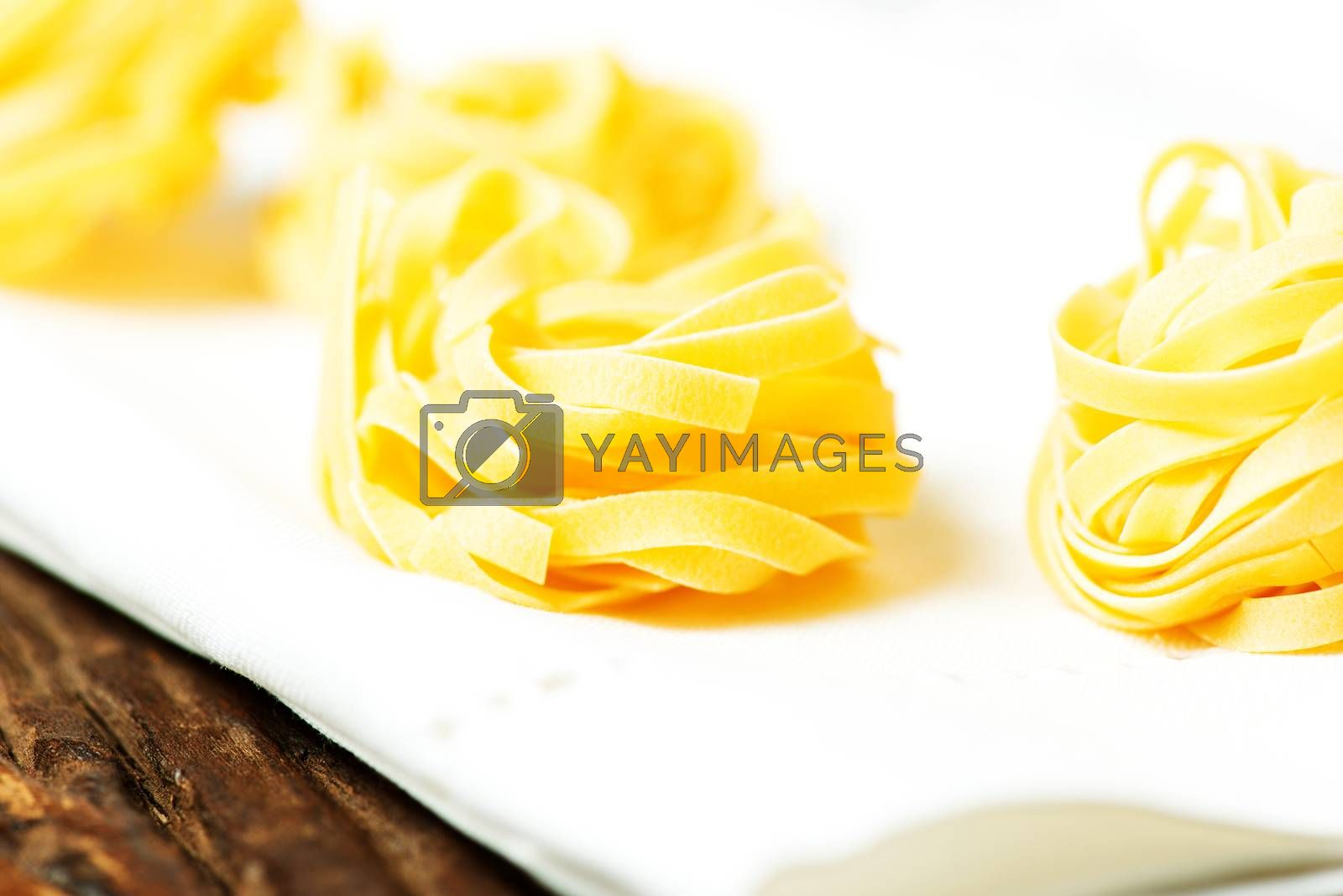Royalty free image of Nests of dry pasta tagliatelle on tablecloth macro by Nanisimova