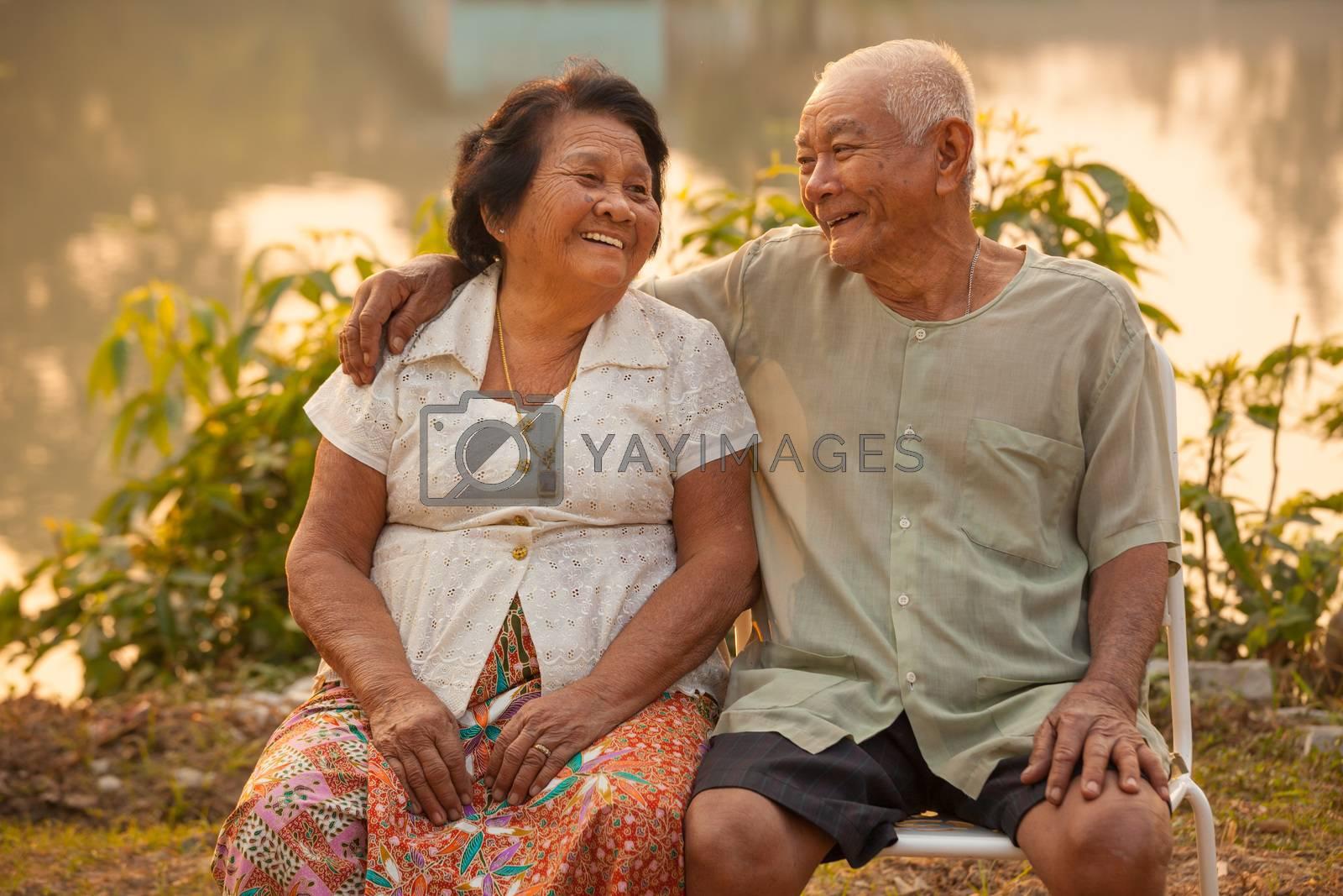Happy Asian Senior couple sitting outdoors on sunset