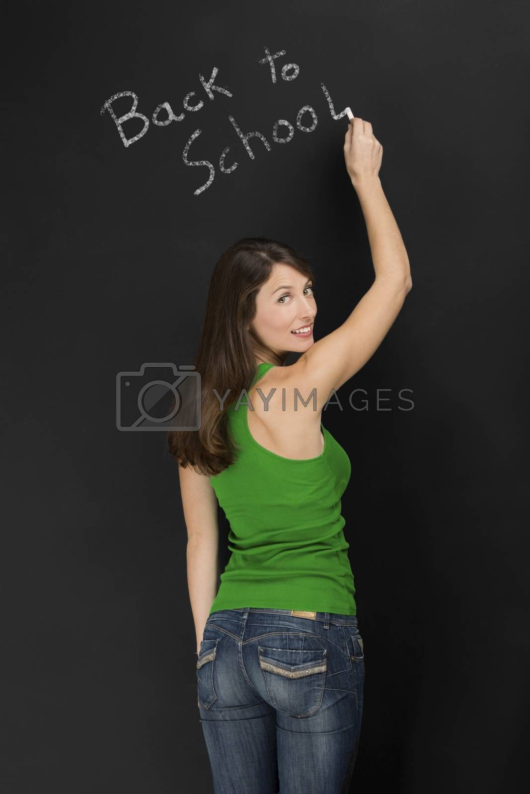 Beautiful young student writing on chalkboard the words back to school