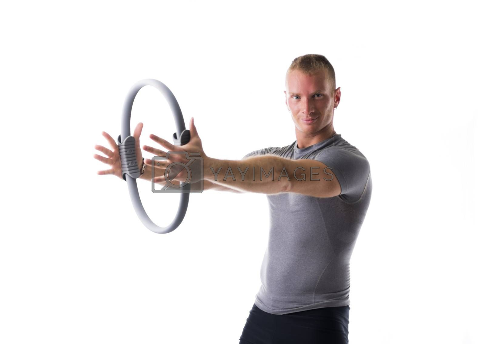 Young muscular man exercising with Pilates ring in front of chest, isolated on white