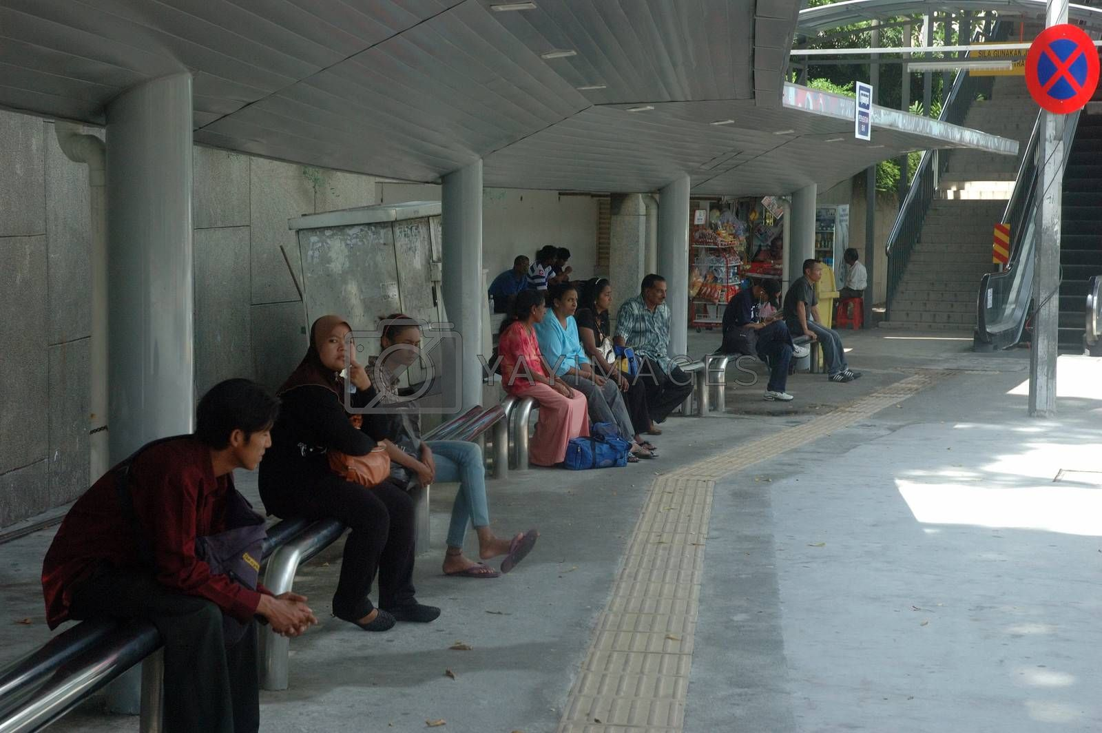 Kuala Lumpur, Malaysia - June 8, 2013: Malaysian people waiting for bus in shelter.