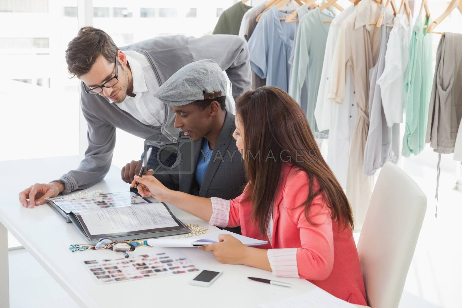 Group of fashion designers discussing designs in a studio