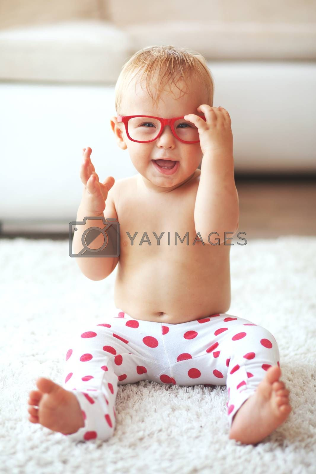 Toddler playing with glasses on a white carpet at home