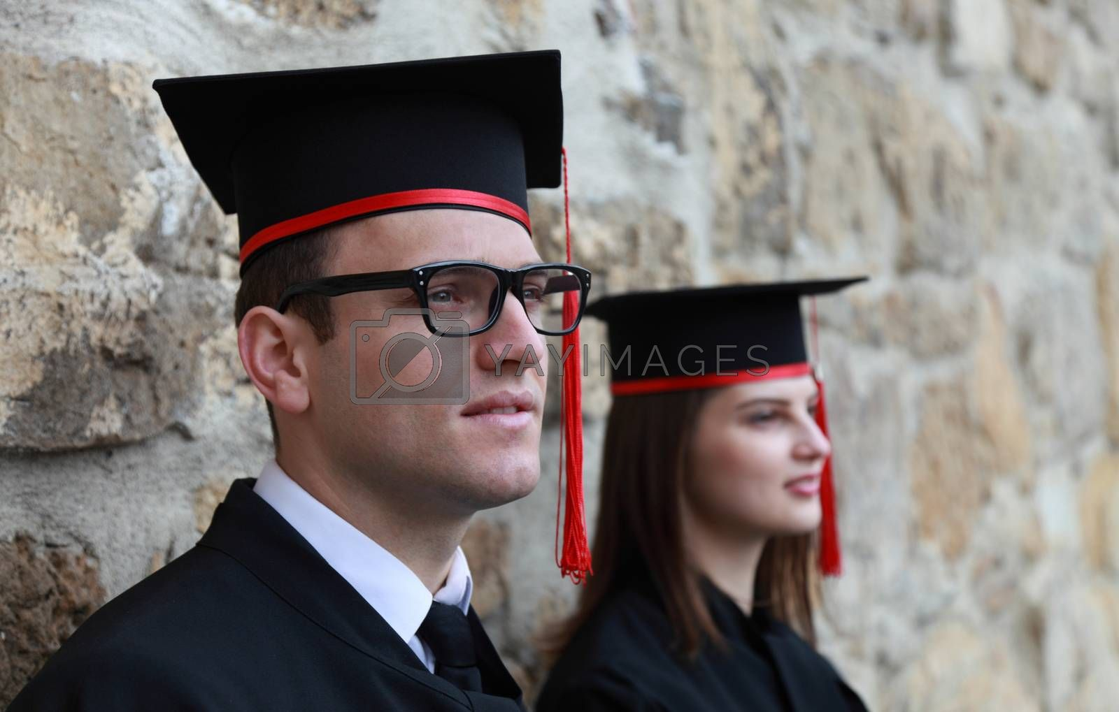 Portrait of a young couple in the gradution day posing near a stoned wall. Selective focus on the man.