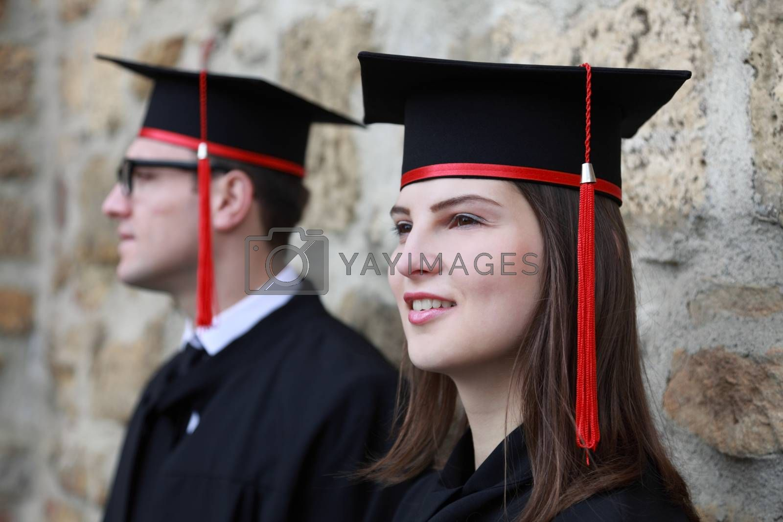 Portrait of a young couple in the gradution day posing near a stoned wall. Selective focus on the woman.
