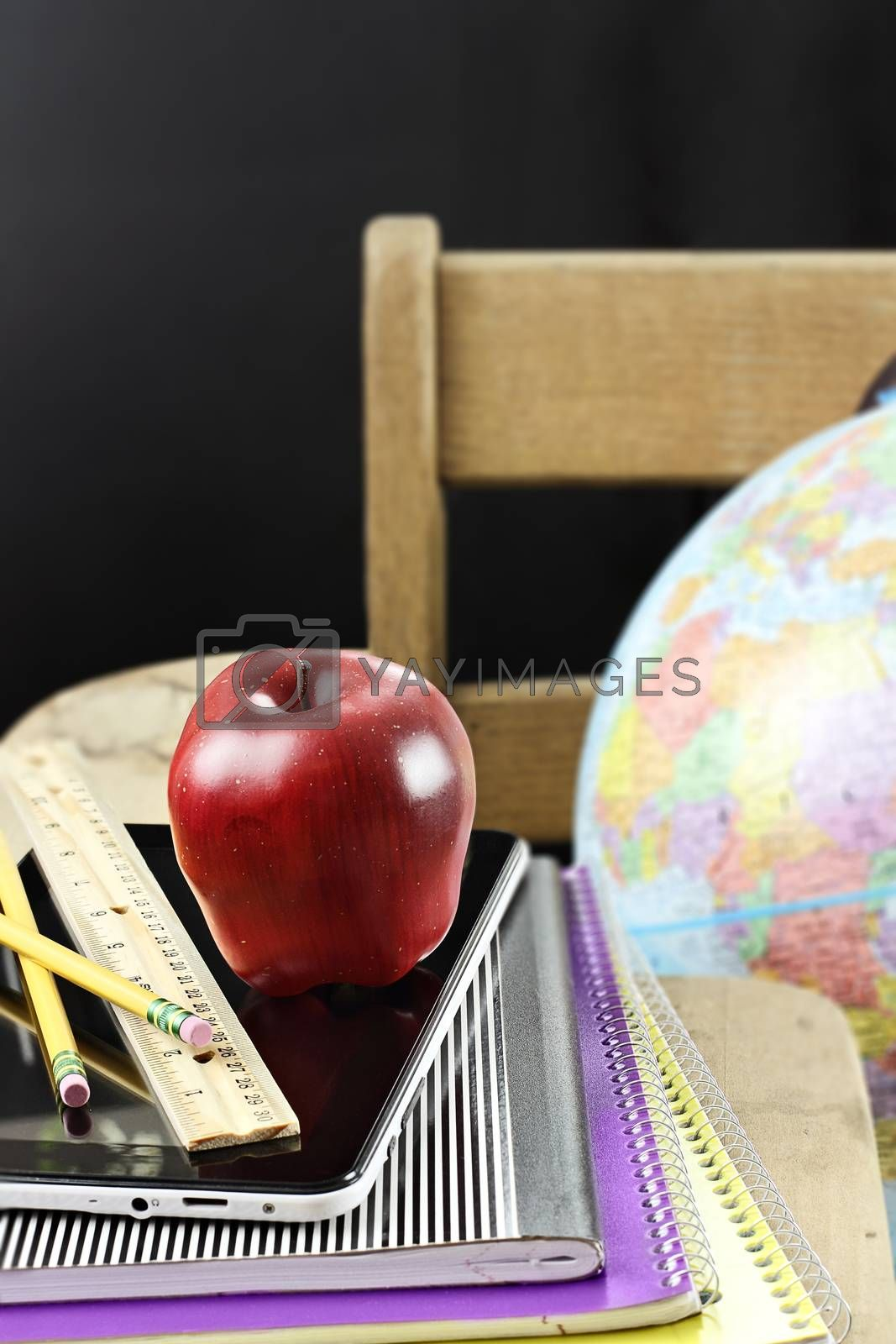 Red apple with school supplies and tablet sitting on an antique school desk.