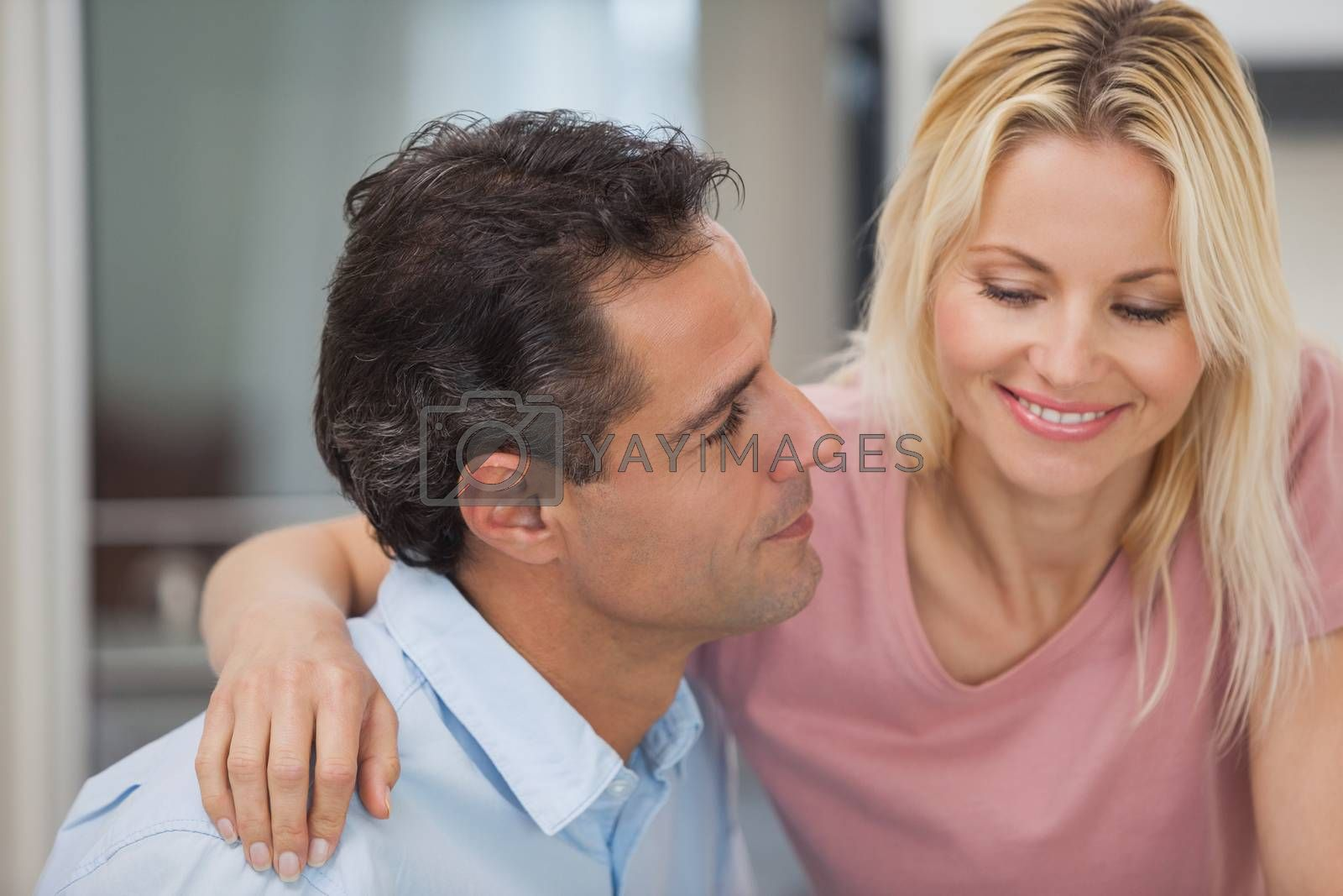 Close-up of a loving man looking at happy woman in the kitchen at home