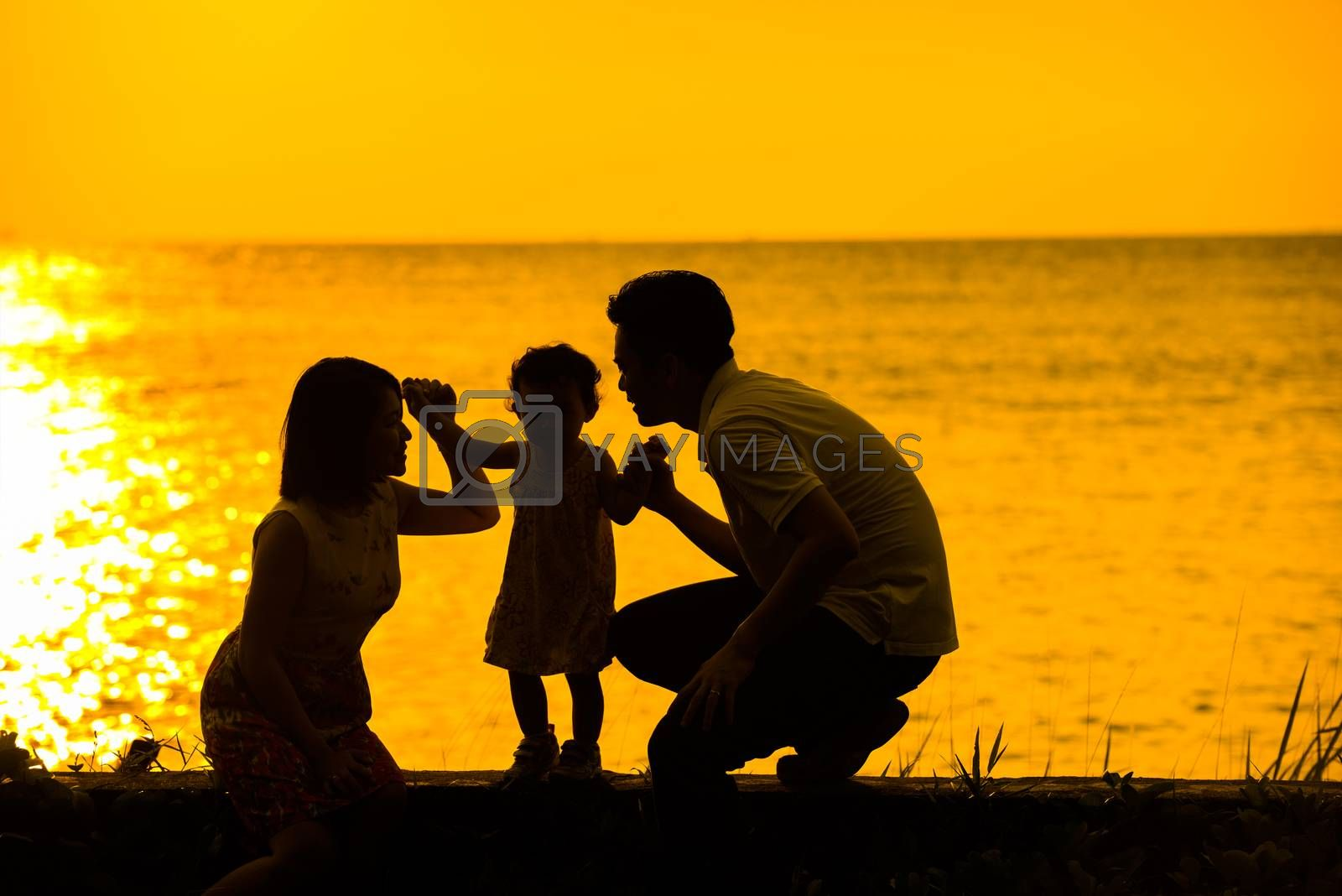 Silhouette of happy Asian family playing at outdoor beach during summer sunset.