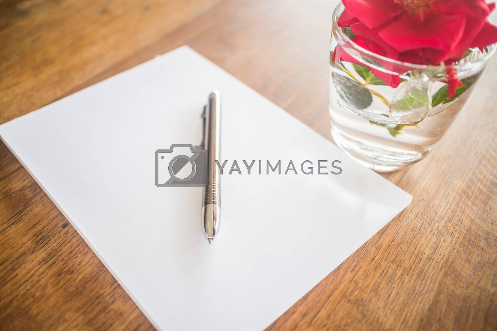Royalty free image of Closeup metal pen on wooden work table by nalinratphi