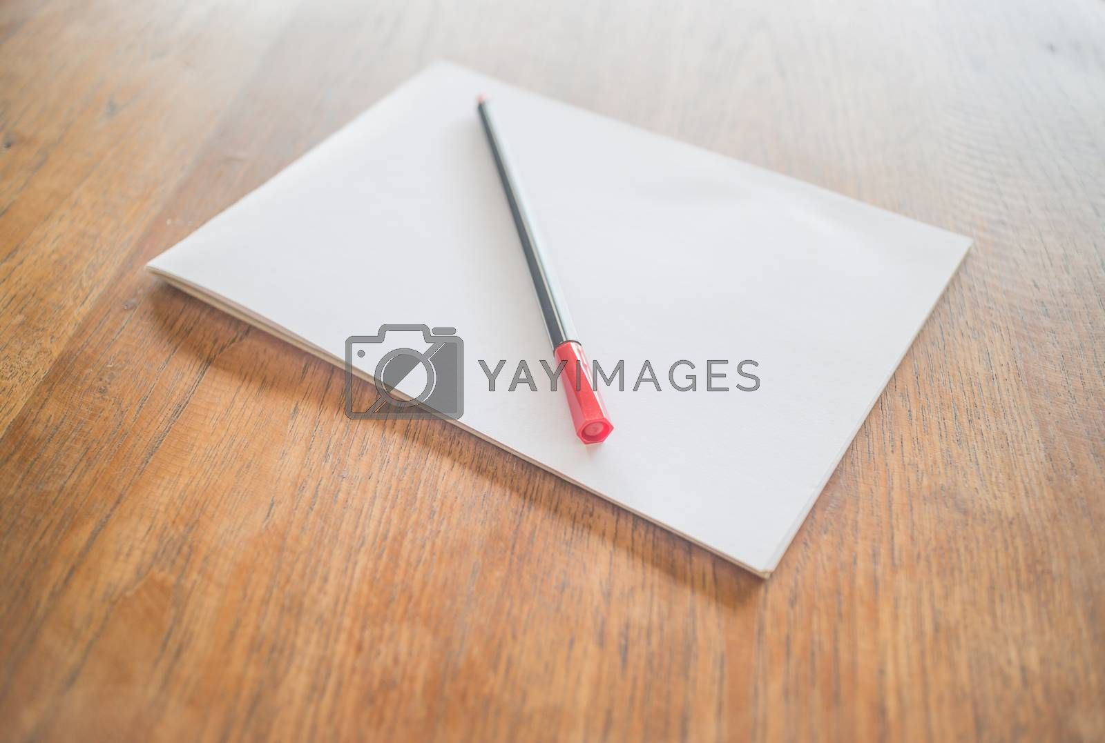 Royalty free image of White paper and red pen on wooden table by nalinratphi