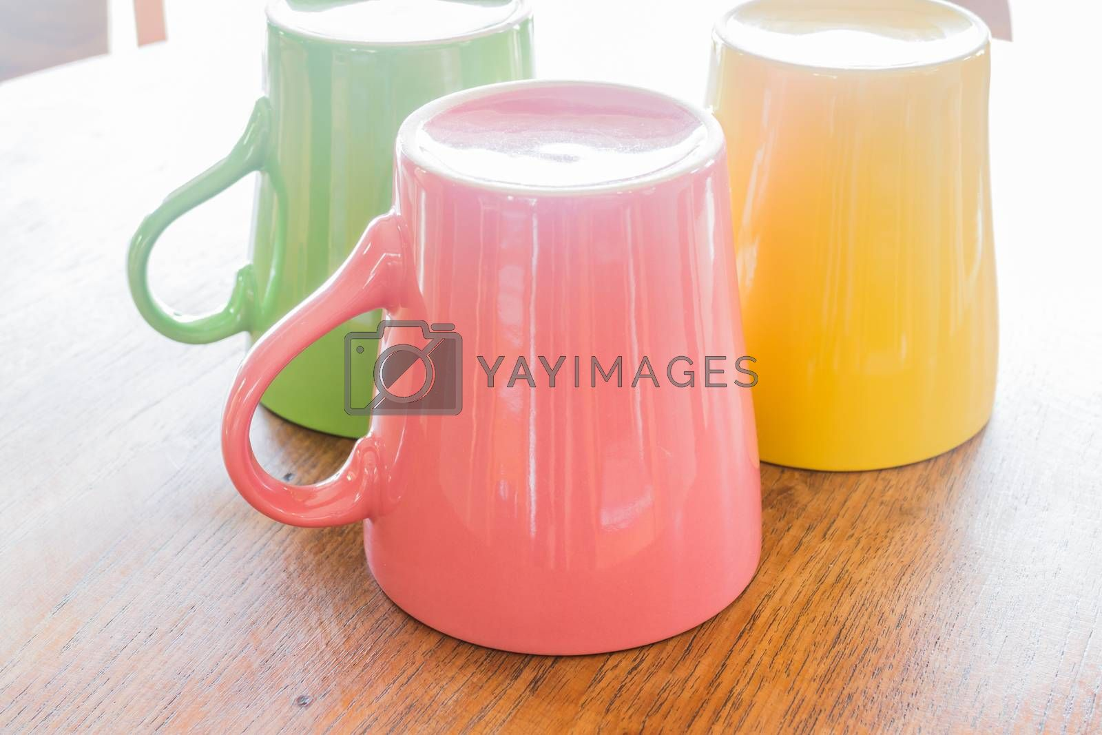 Royalty free image of Colorful ceramic cups on wooden table by nalinratphi