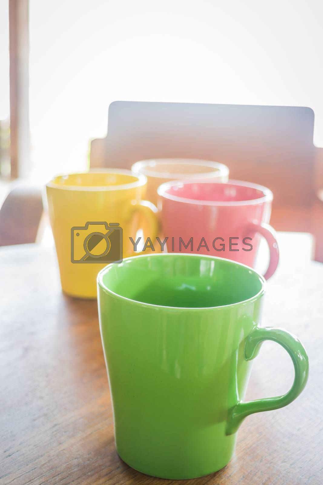Royalty free image of Colorful ceramic coffee cups on wooden table by nalinratphi