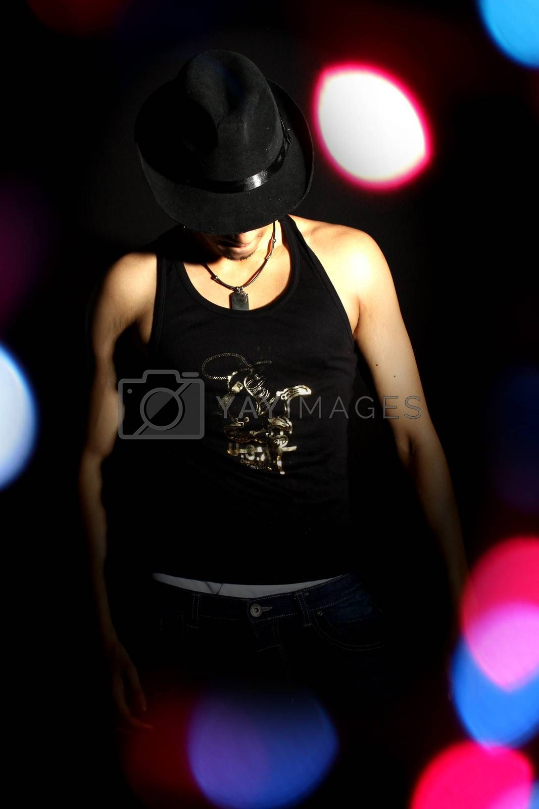 Royalty free image of A Stylish Dancer in a spotlight and colorful lights by thefinalmiracle
