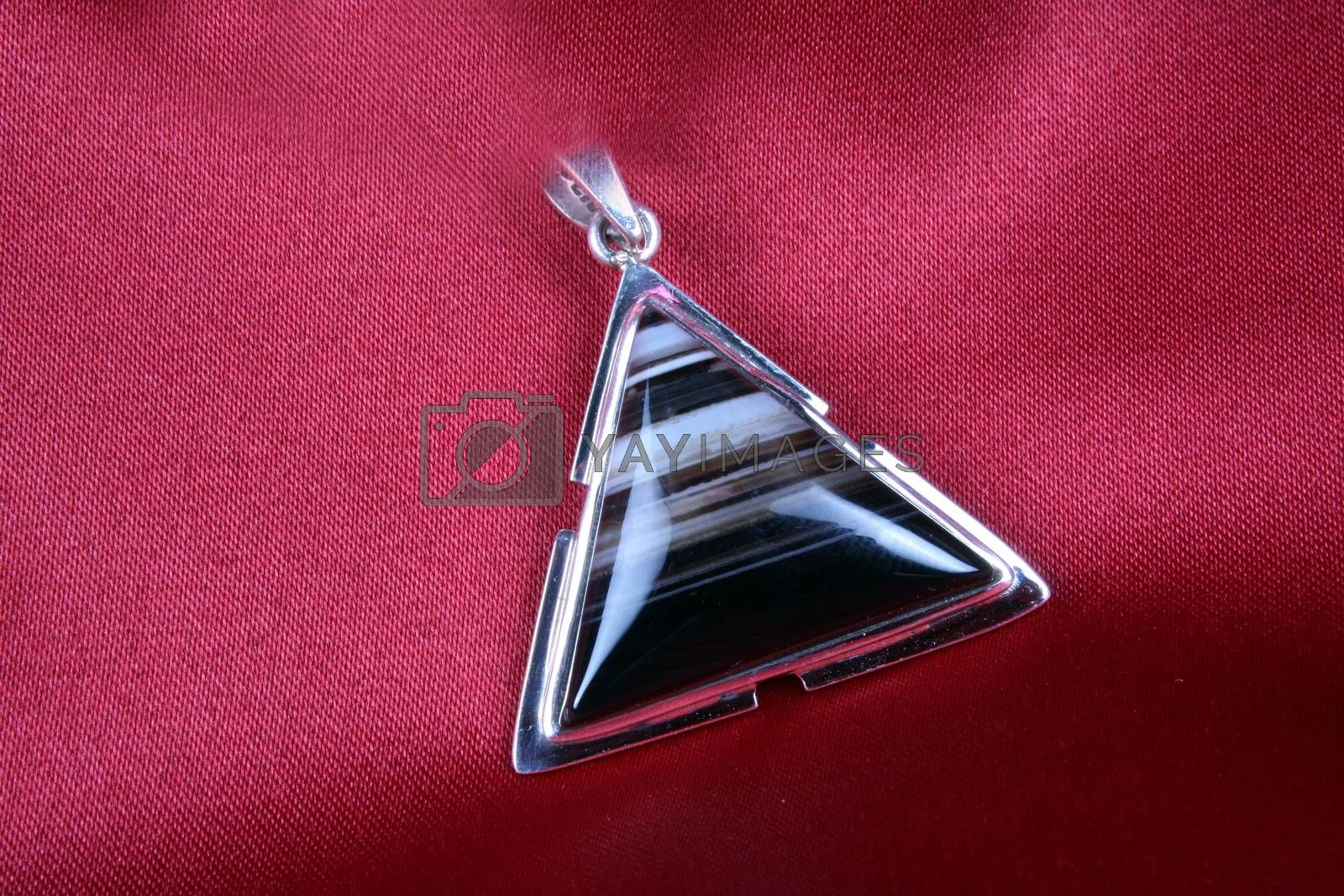 Royalty free image of An antique Triangular Silver Pendant with Jasper stone kept on a by thefinalmiracle