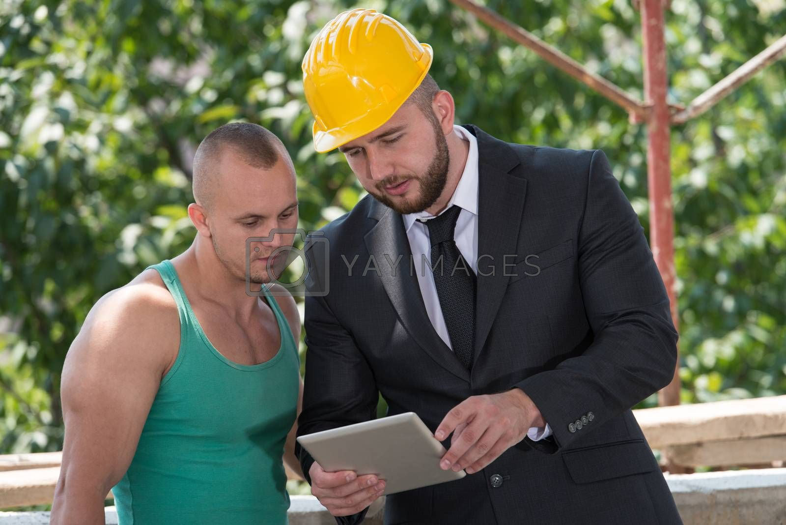 Royalty free image of Businessman And Industrial Worker Looking At Tablet PC by JalePhoto