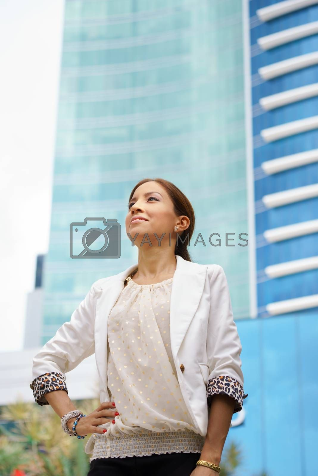 Royalty free image of Business woman walking proud city office building by diego_cervo