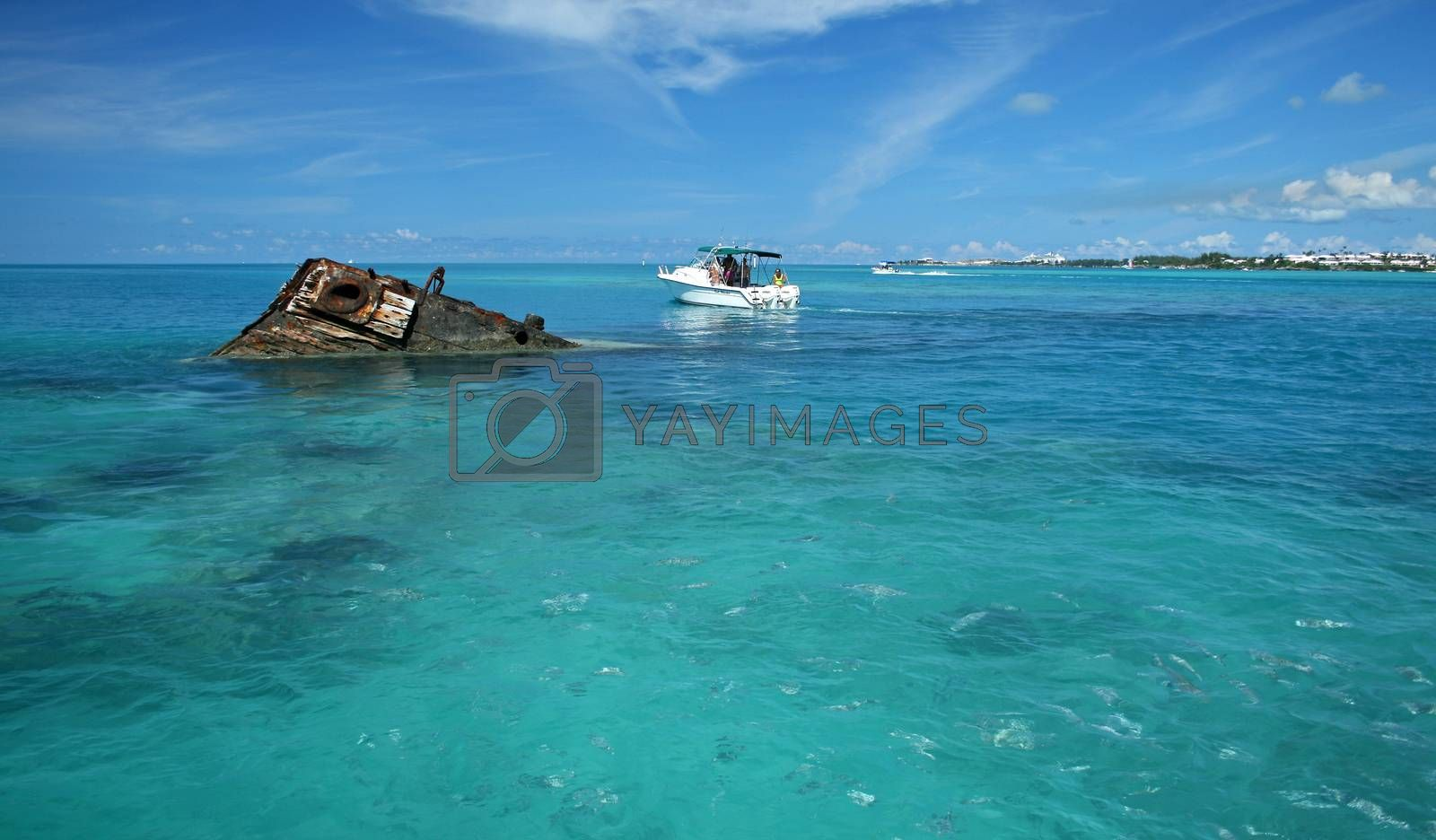 A ship wreck in a tropical sea, with a pleasure boat floating close by