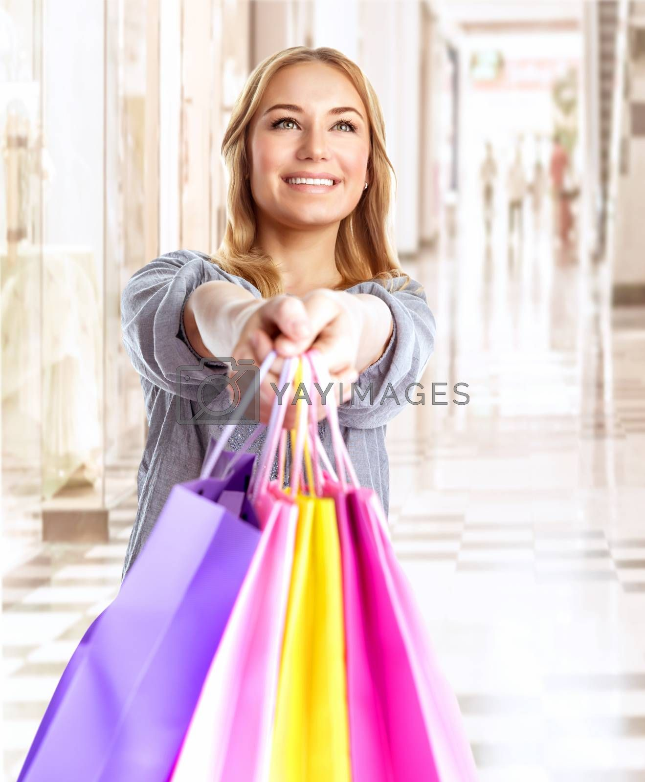 Happy girl with colorful shopping bag, cheerful young female doing purchase in great luxury retail store, spending money with pleasure concept