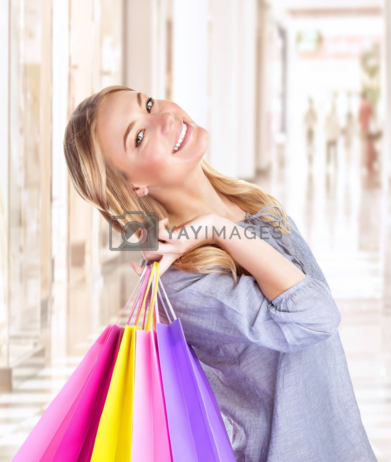 Portrait of happy girl with colourful shopping bag, cheerful young female doing purchase in great luxury retail store, spending money with pleasure concept