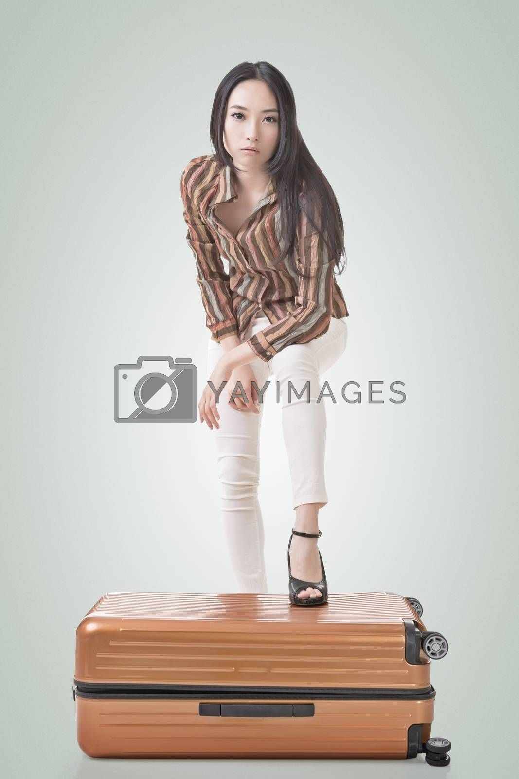 Modern Asian woman stand on a luggage, full length portrait on white background.