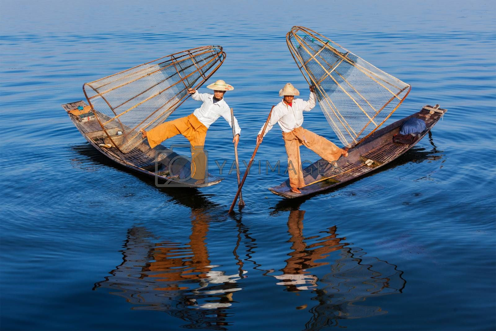Myanmar travel attraction landmark - Traditional Burmese fishermen balancing with fishing net at Inle lake in Myanmar famous for their distinctive one legged rowing style