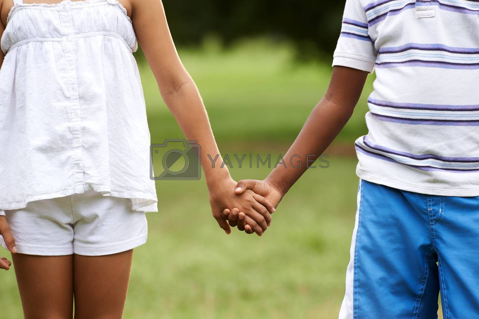 Interracial people in love with caucasian little girl and african boy holding hands in park. Cropped view