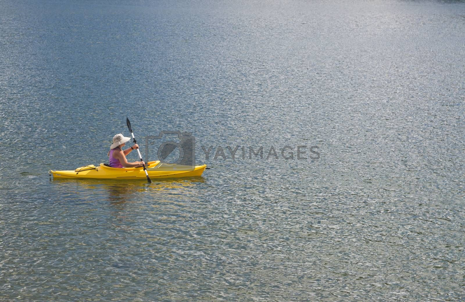 Woman Kayaking on Beautiful Peaceful Mountain Lake.
