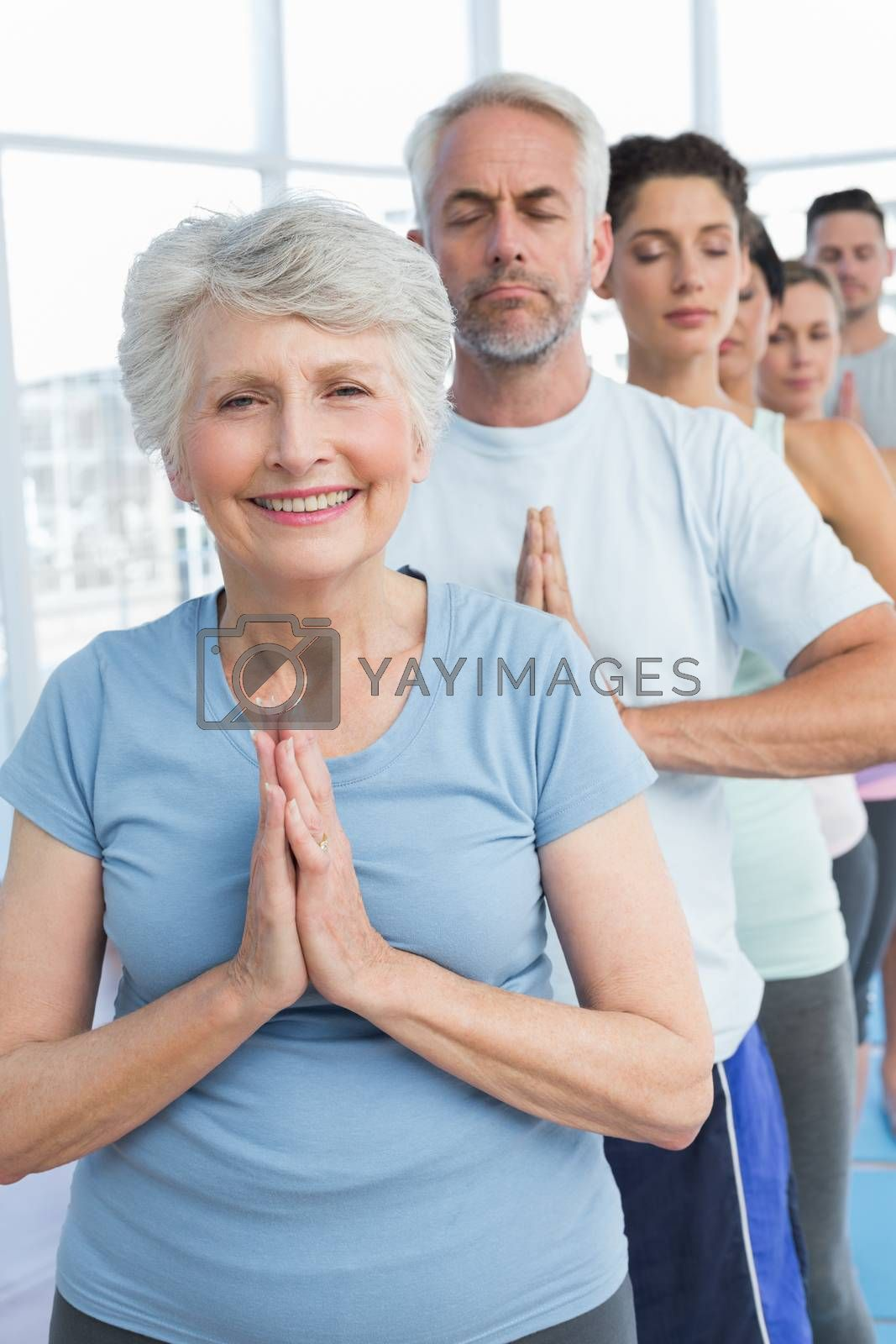 Portrait of sporty people with joined hands at a bright fitness studio