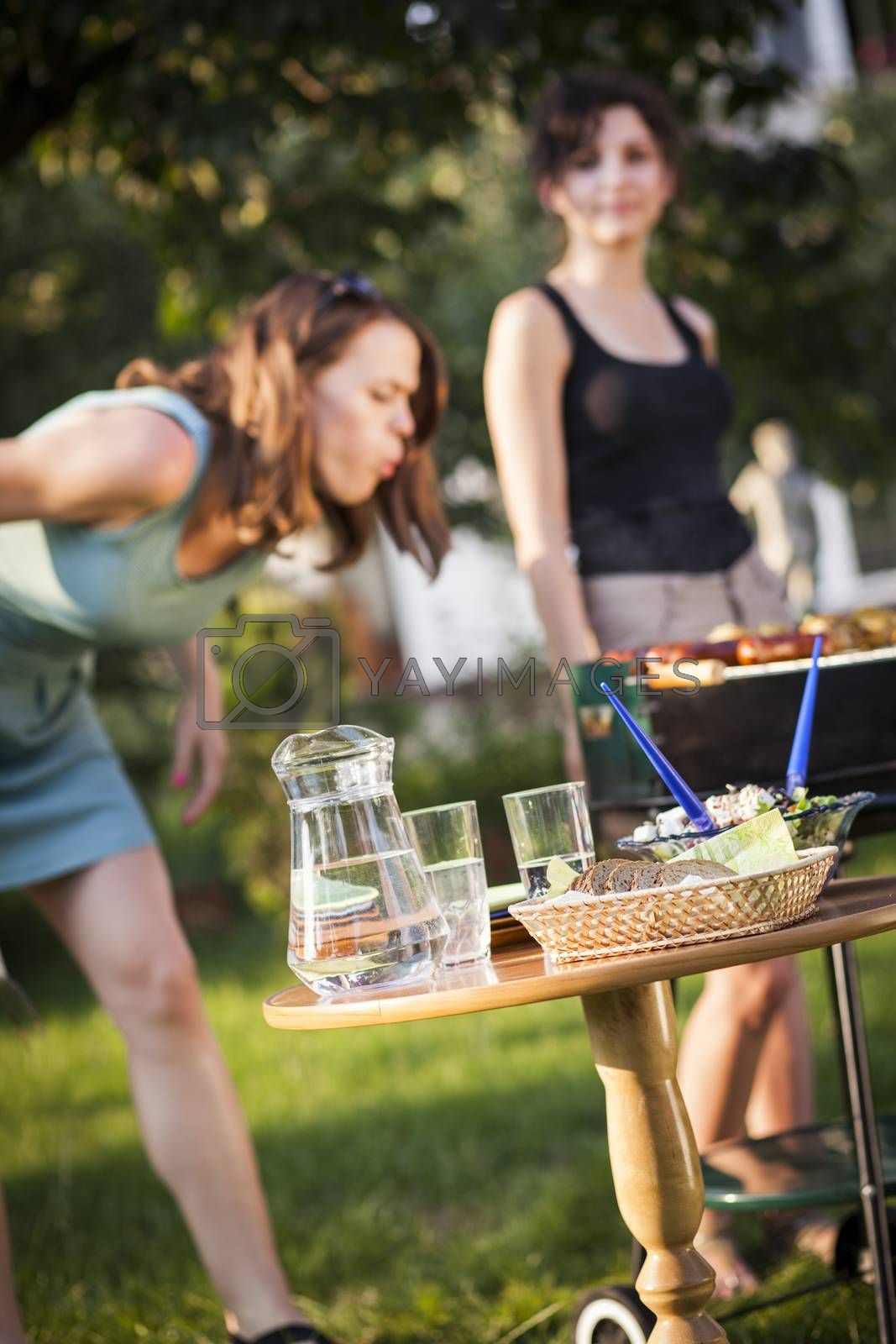 Royalty free image of Two pretty girls making food on grill by fikmik