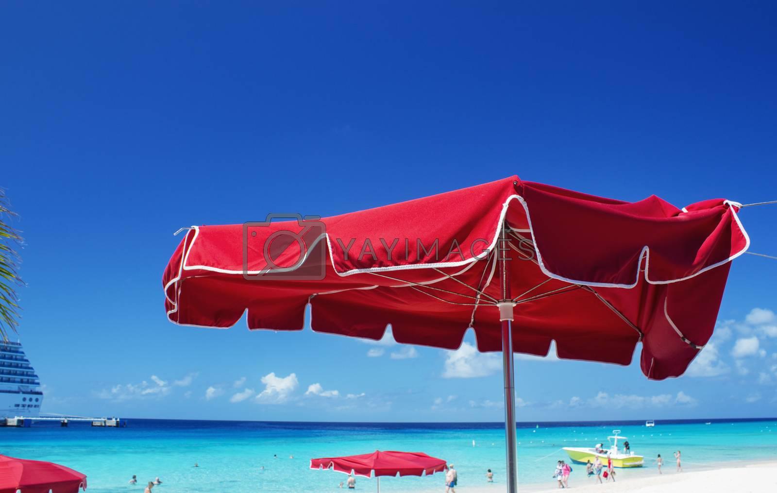 Colourful red umbrella on a tropical beach.