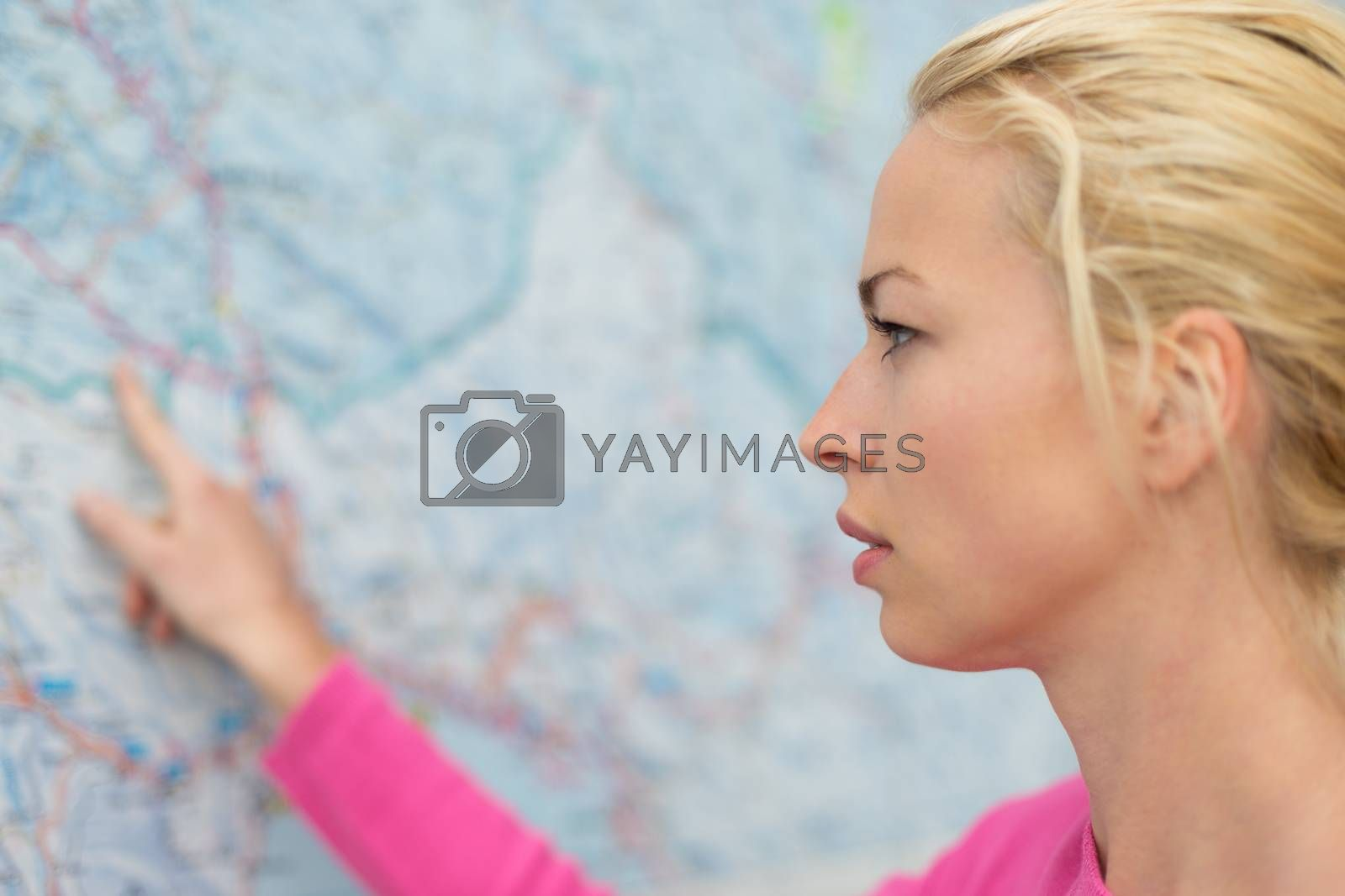 Woman orientating herself on the public transport map pointing on her final destination.
