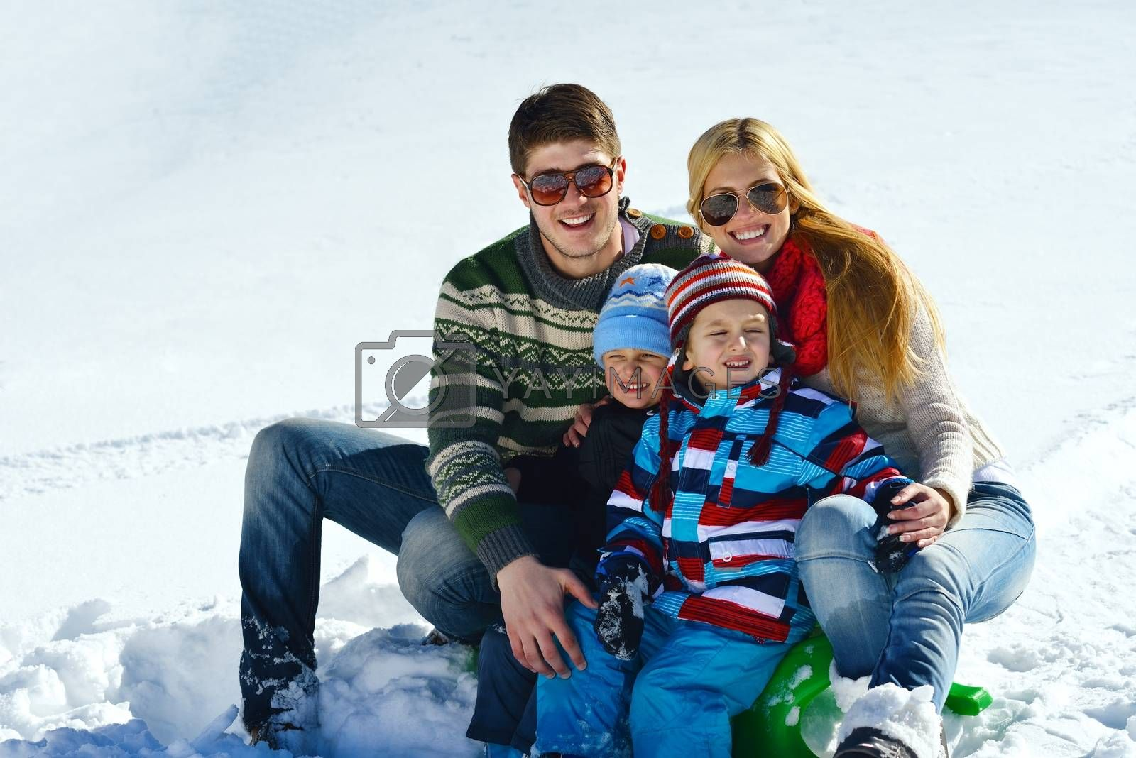 family having fun on fresh snow at winter vacation by .shock