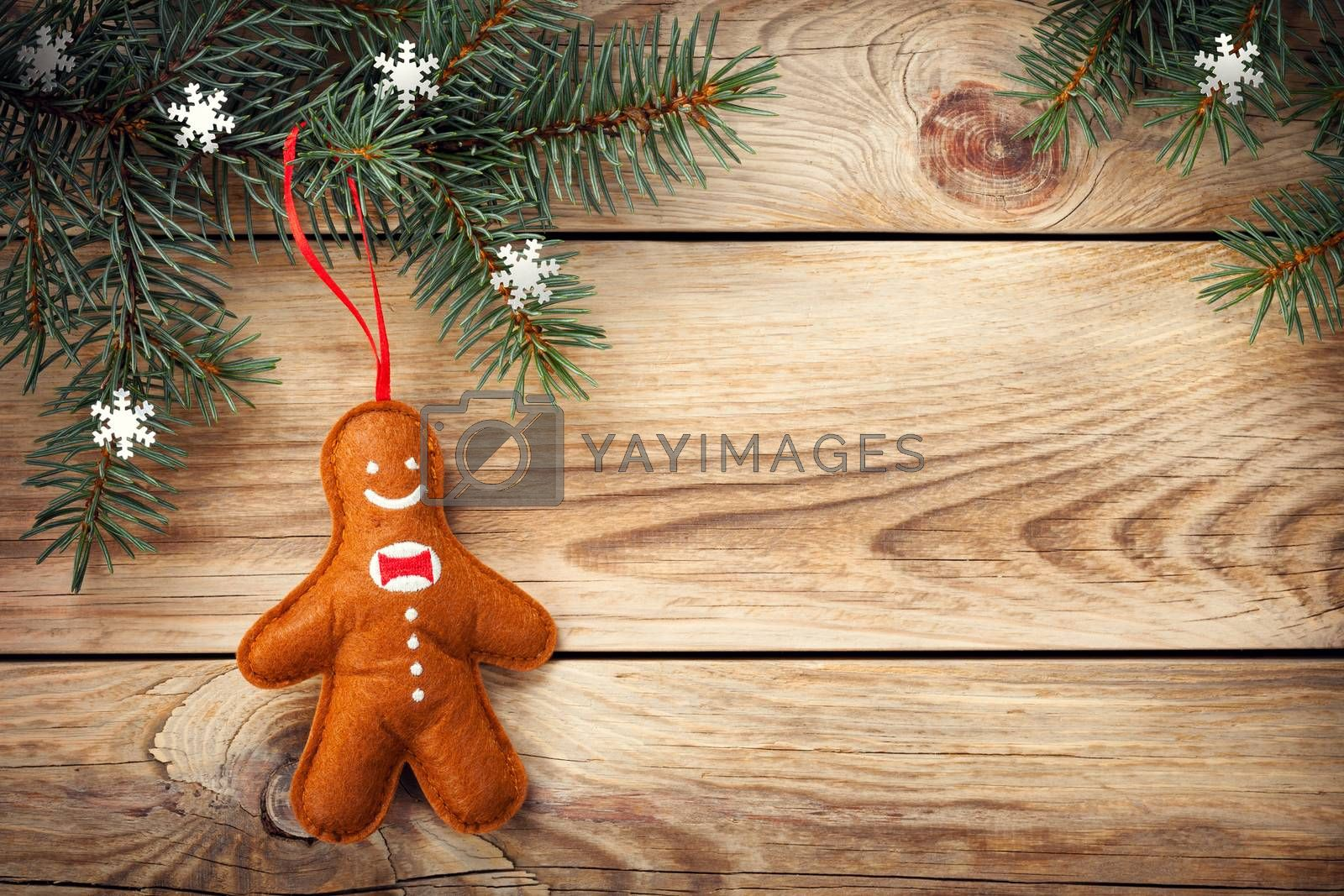 Christmas background with spruce tree and gingerbread man on wooden table. Copy space. Top view