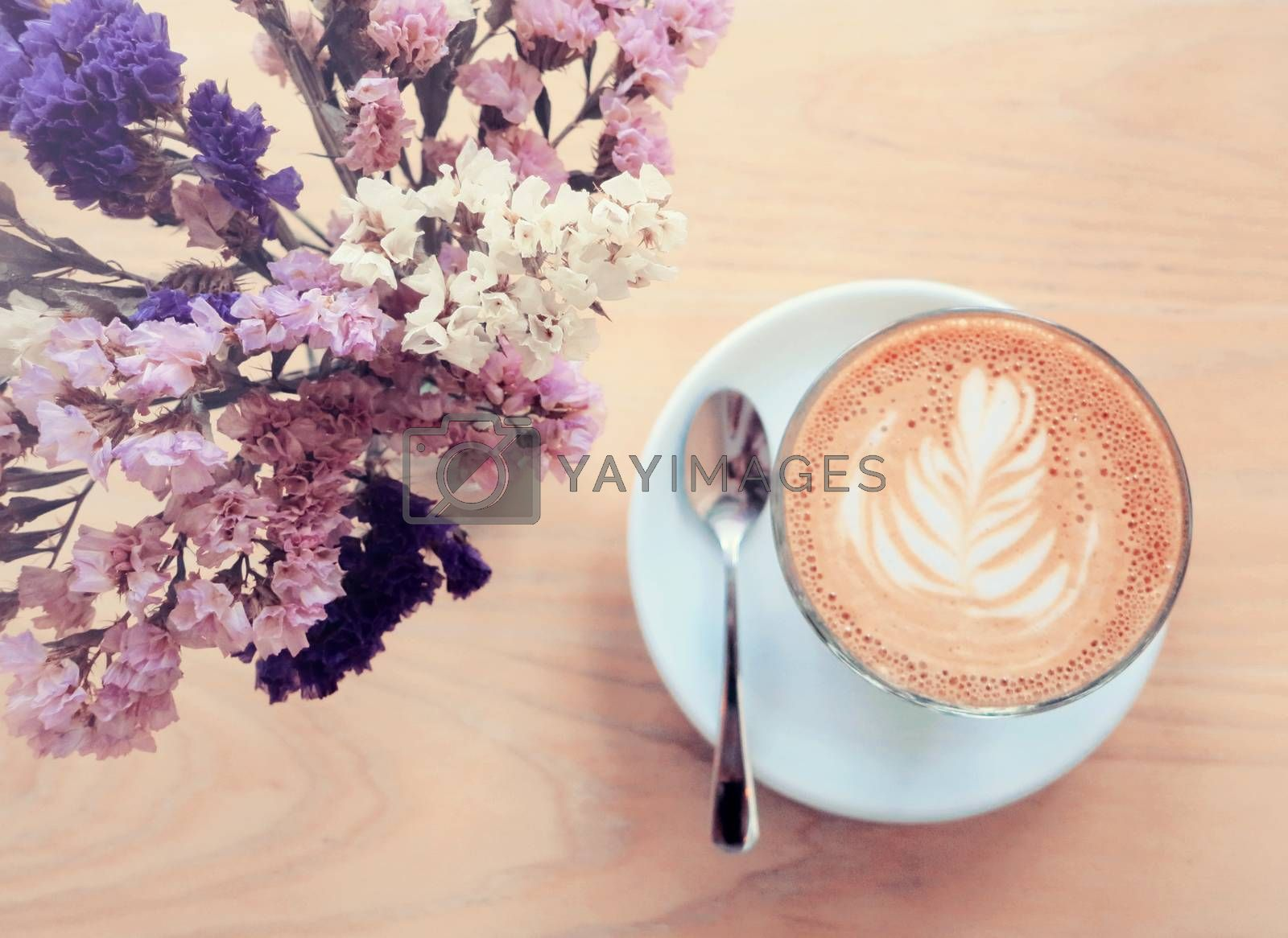 Cup of latte or cappuccino coffee and flowers with retro filter effect