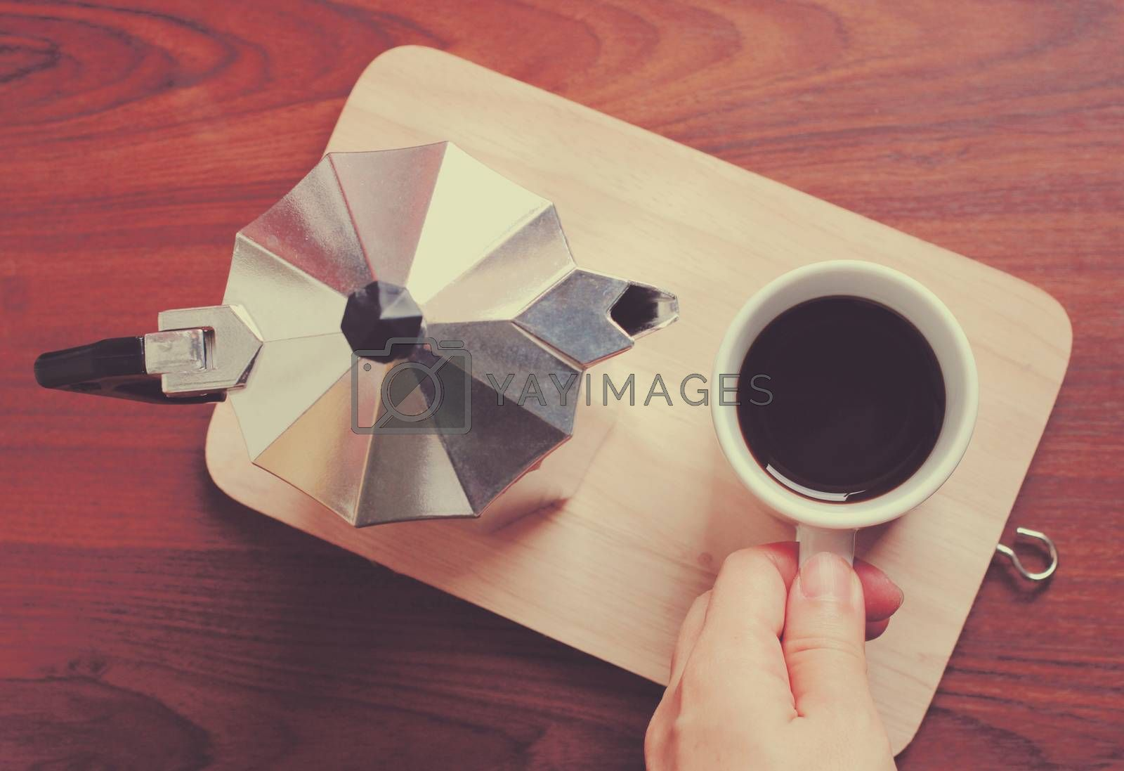 Hand holding coffee cup and moka pot with retro filter effect