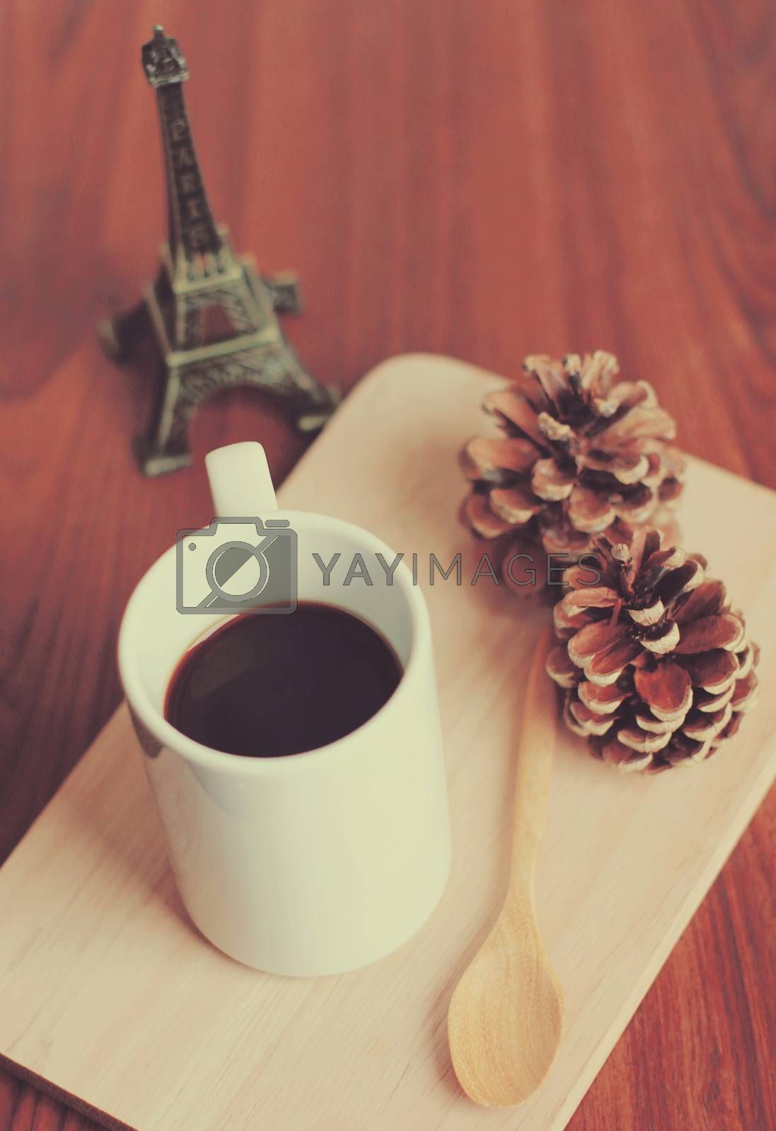 Black coffee and spoon on wooden tray with pine cone, retro filter effect