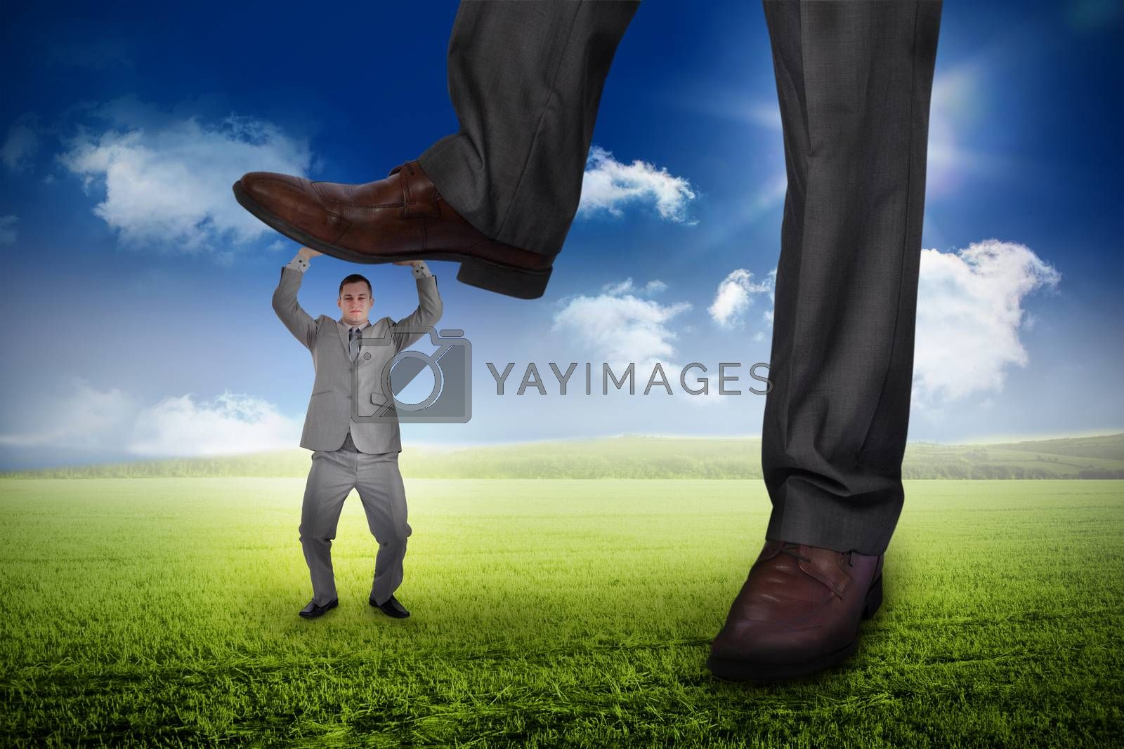 Composite image of businessman stepping on tiny businessman against sunny green landscape