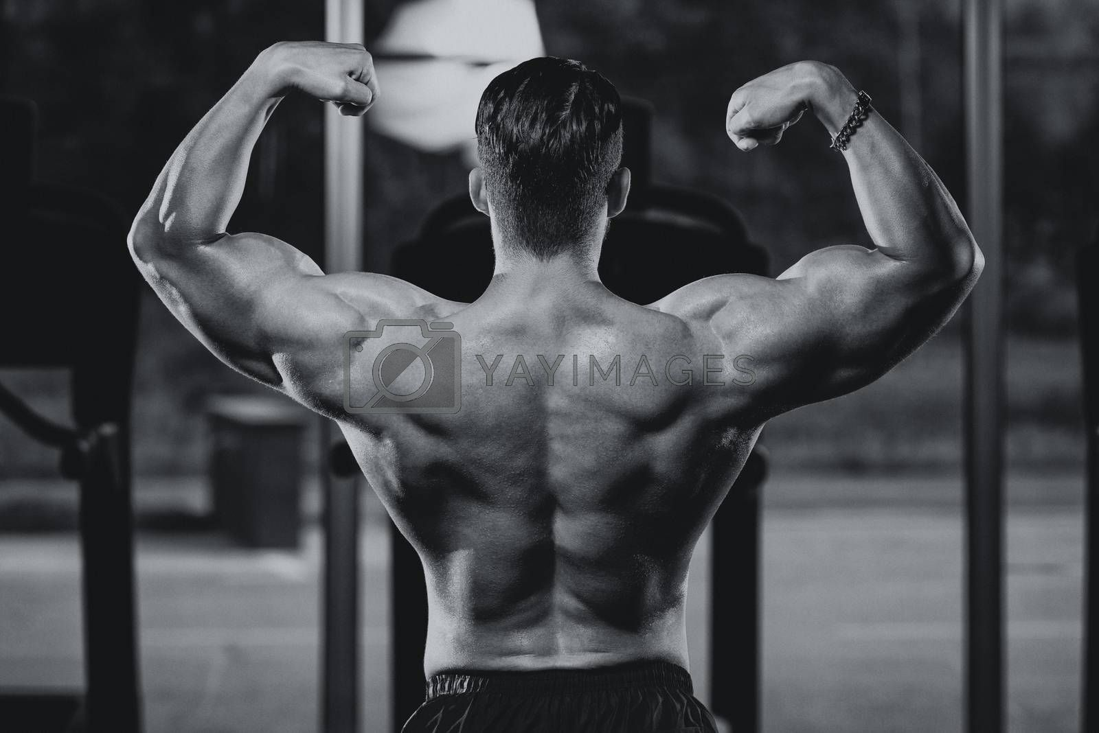 Serious Man Bodybuilder Standing In The Gym And Flexing Muscles