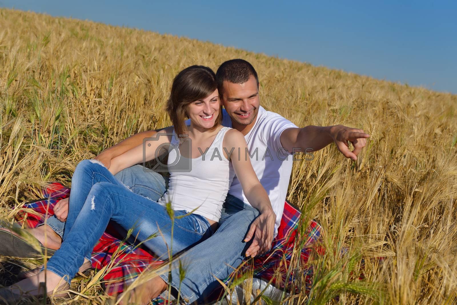 happy couple in wheat field by .shock