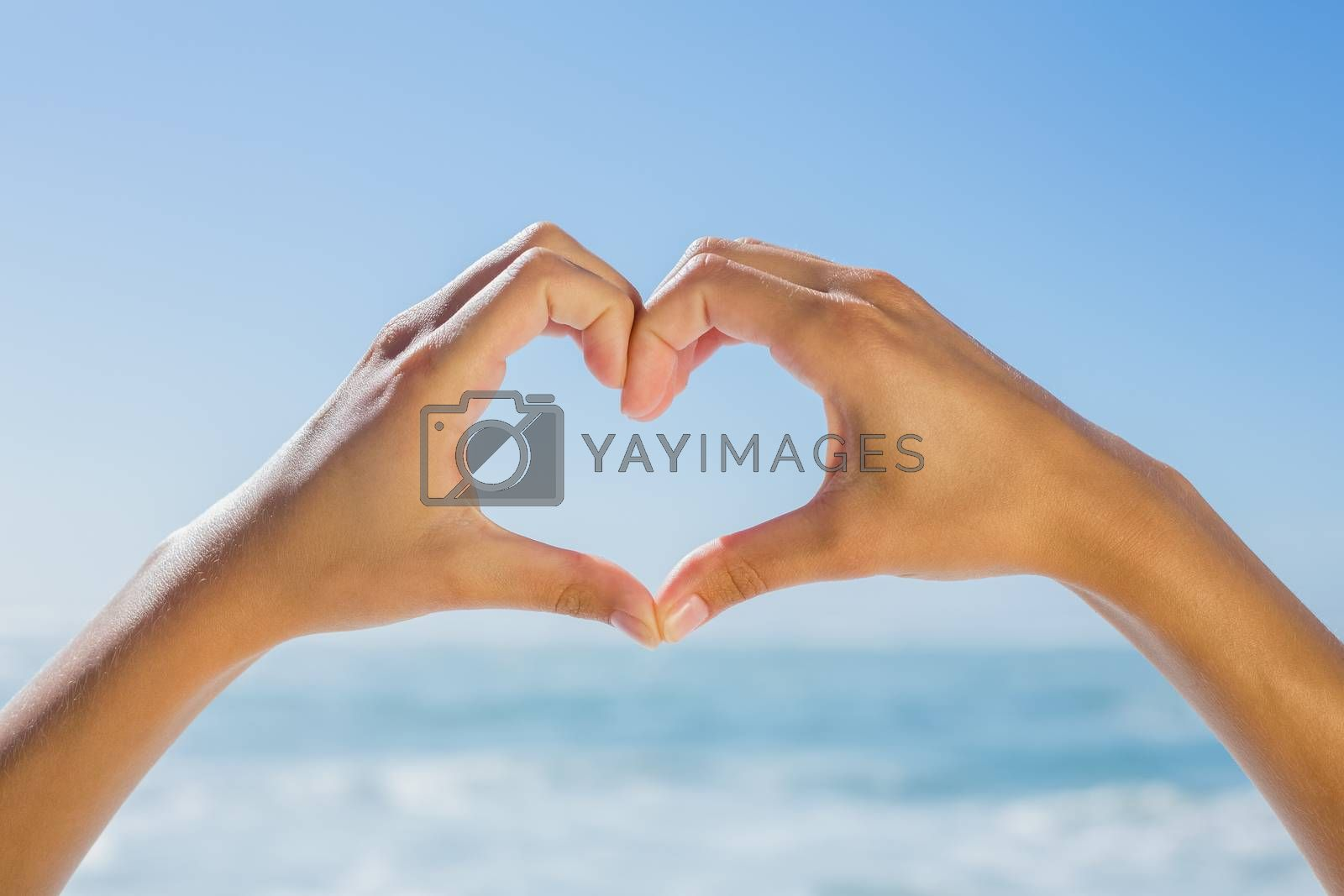 Female hands making heart shape by the sea on a sunny day