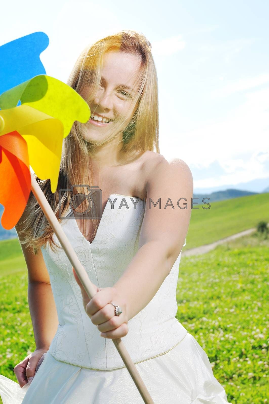 happy young beautiful bride after wedding ceremony event have fun outdoor on meadow at sunset with windmill toy and representing smart energy